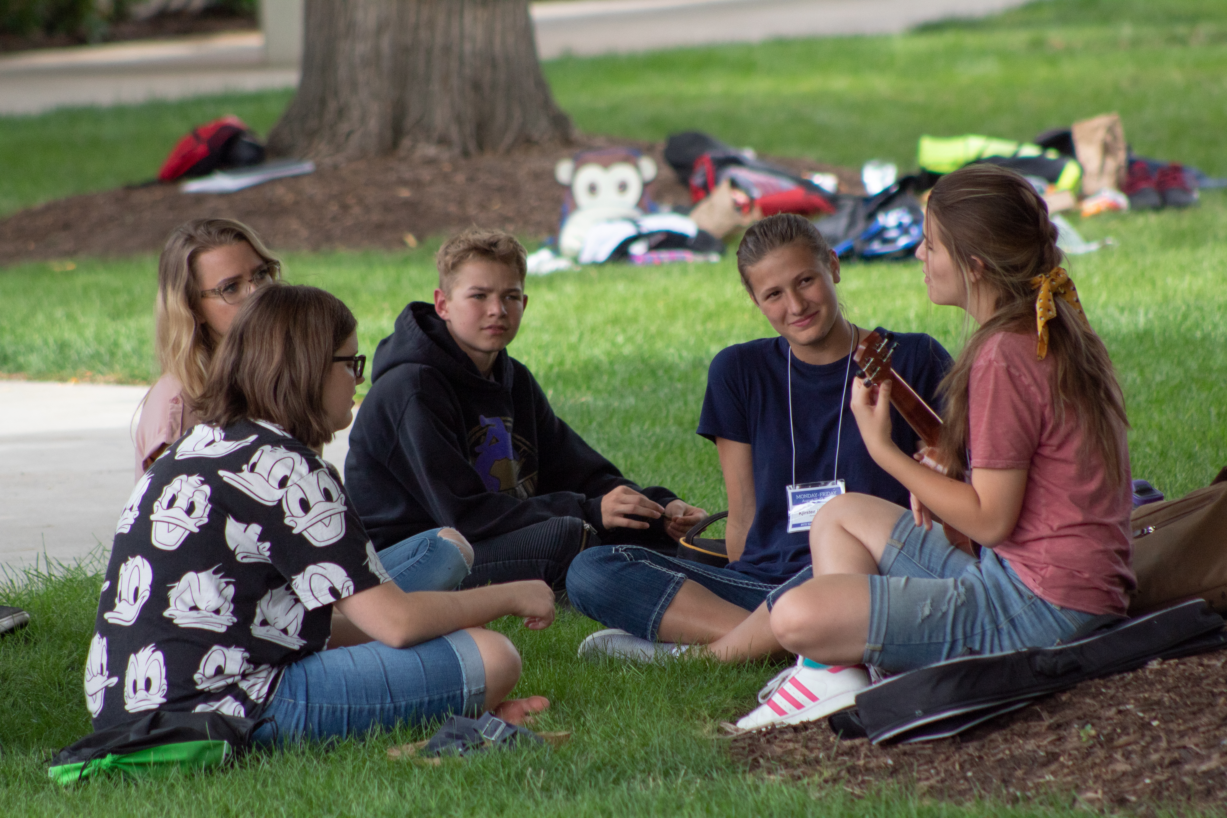 Youth sit on the grass and sing together just outside the Richards Building between Education Week classes at BYU.