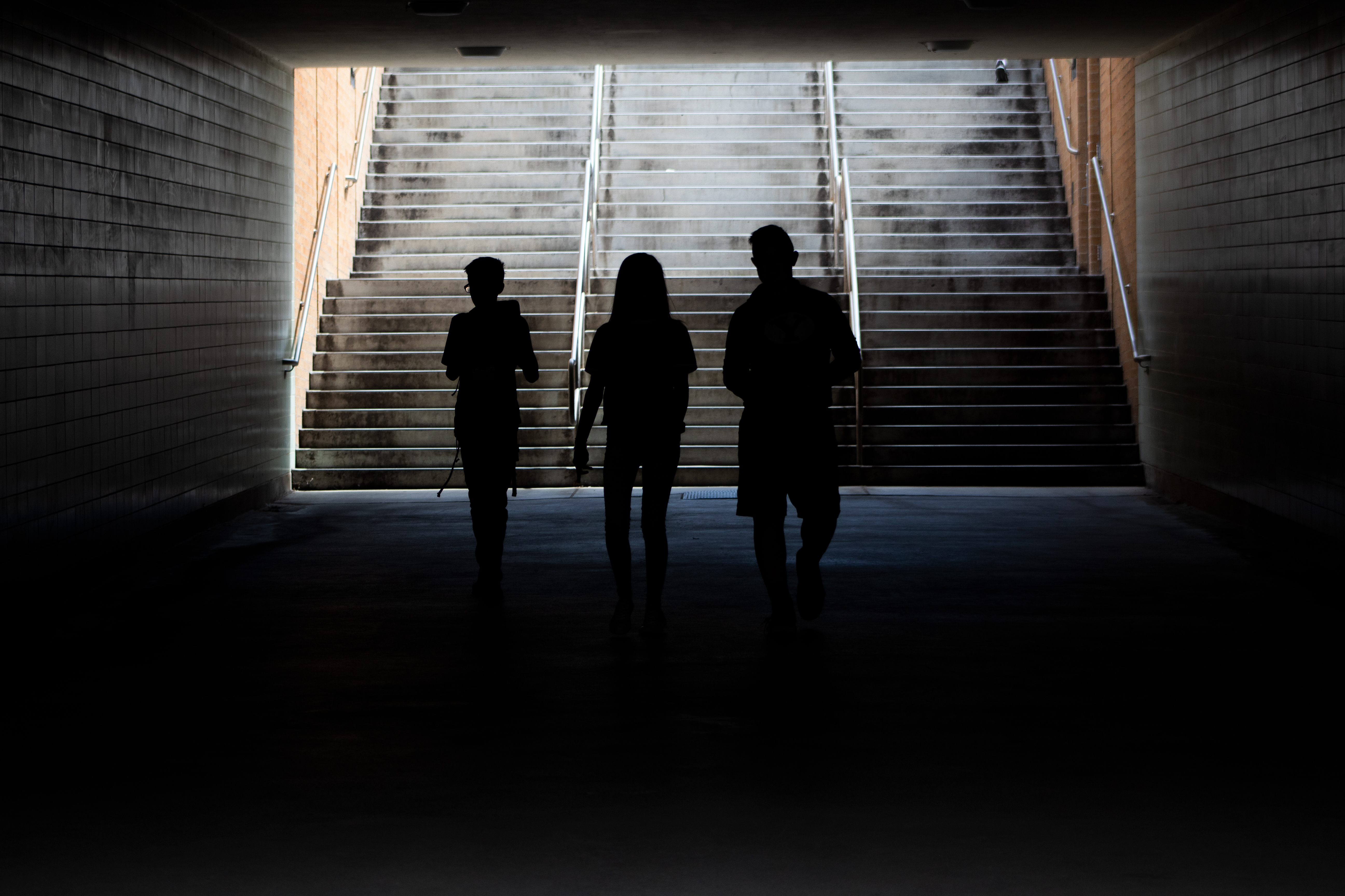 Silhouetted youth walk through the tunnel toward the Richards Building at BYU during Education Week.