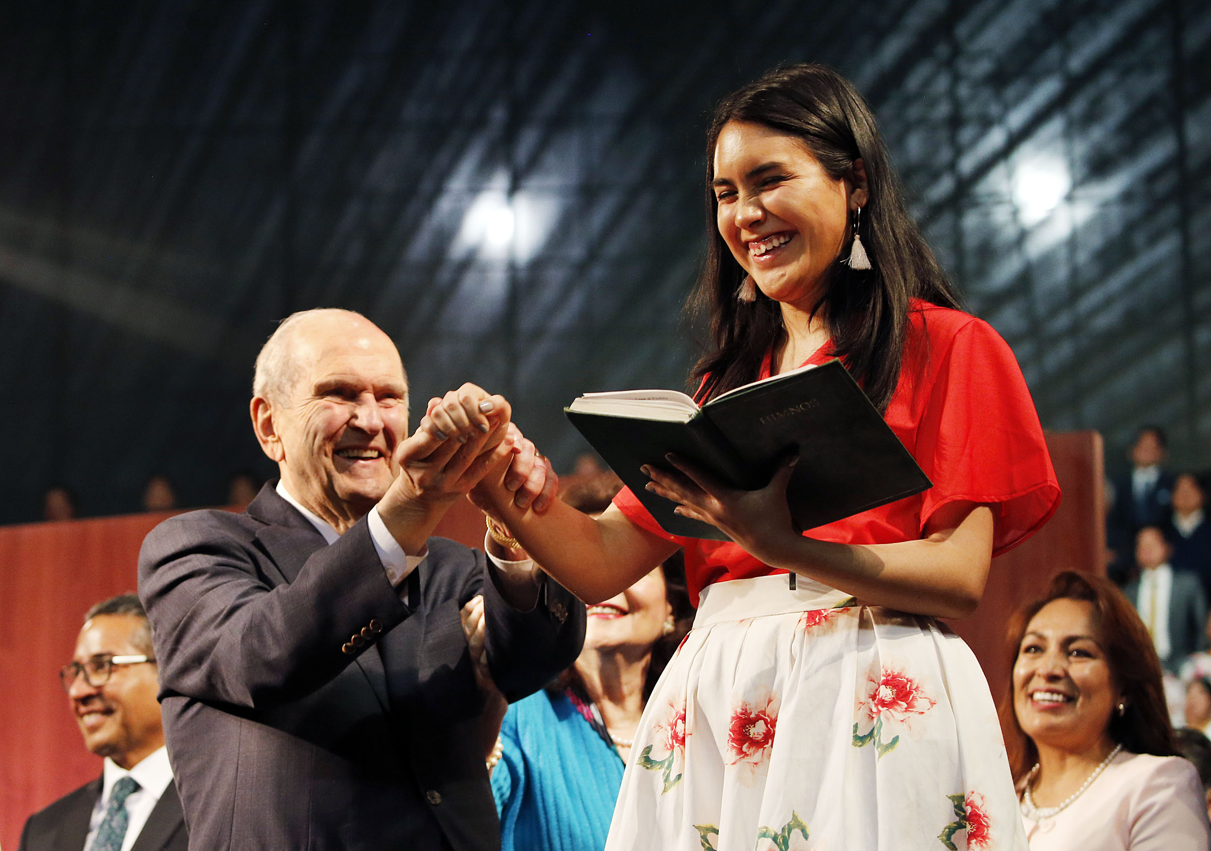 President Russell M. Nelson of The Church of Jesus Christ of Latter-day Saints helps Isabela Castellano as she directs a song at the end of a Latin America Ministry Tour devotional in Quito, Ecuador, on Monday, Aug. 26, 2019.