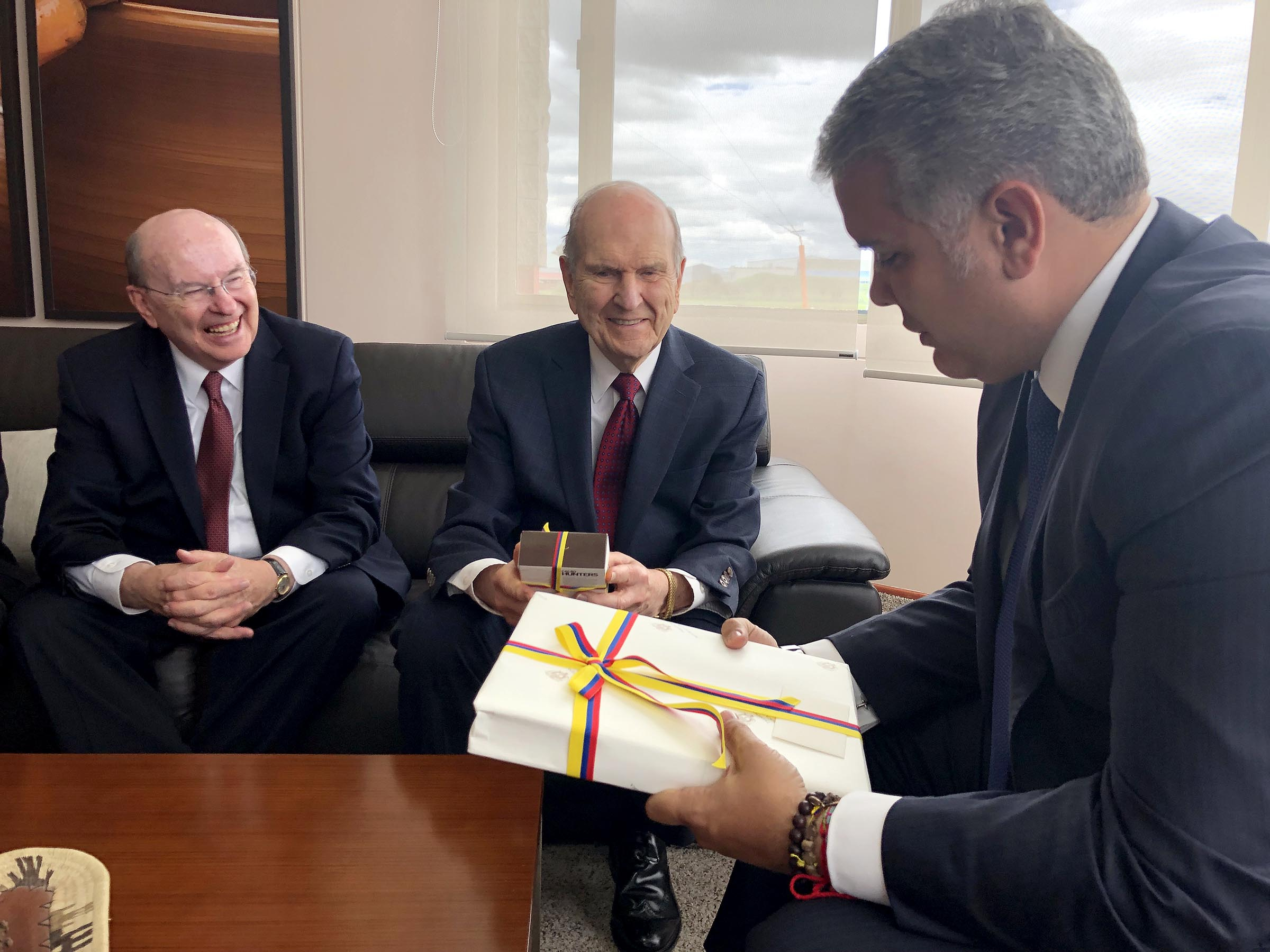 President Russell M. Nelson of The Church of Jesus Christ of Latter-day Saints, center, and Elder Quentin L. Cook of the Quorum of the Twelve Apostles, left, present gifts as they meet with Colombia President Iván Duque Márquez, right, in Bogota, Colombia, Monday, Aug. 26, 2019.
