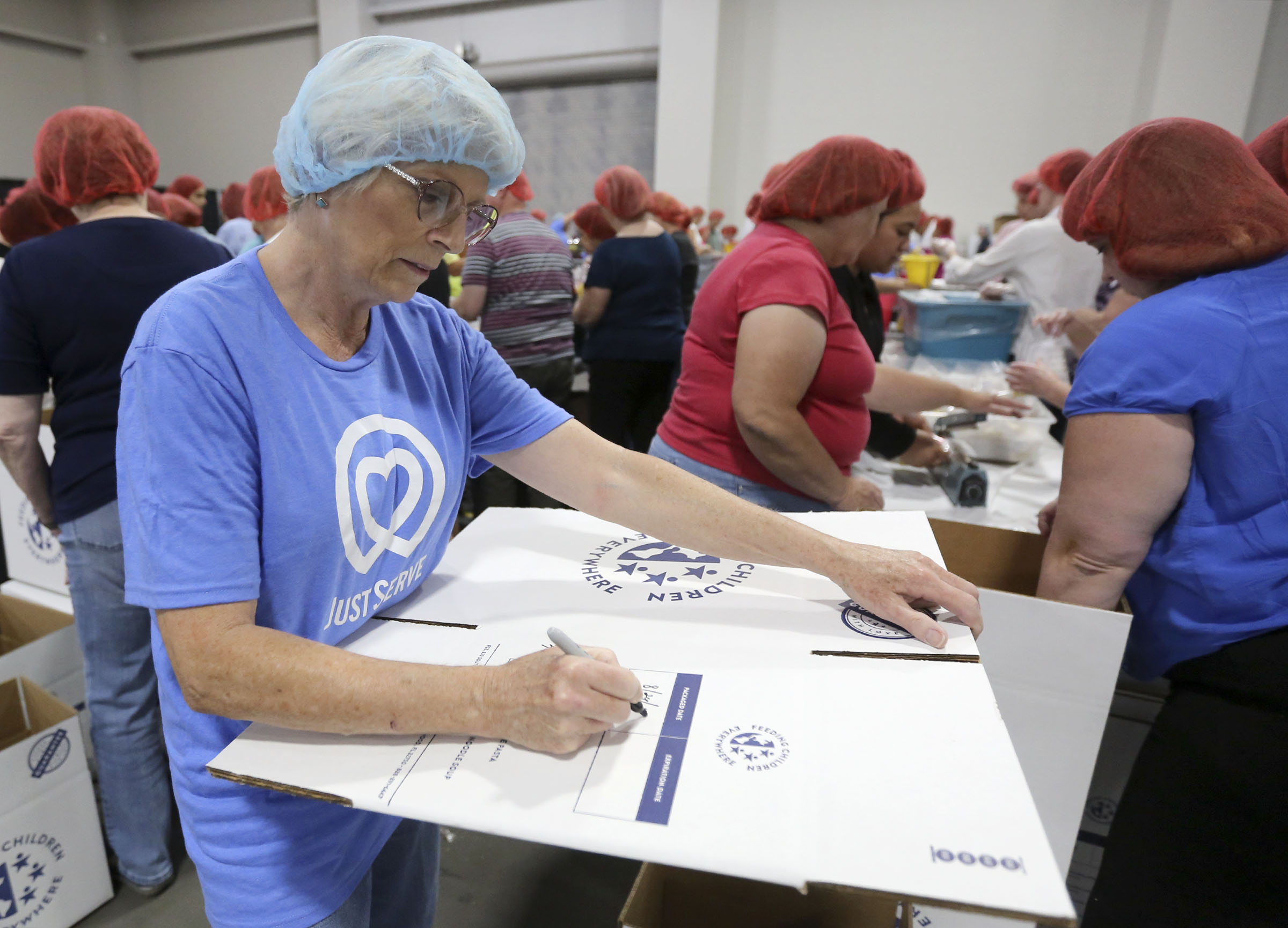 Joy Nelson labels boxes for a service project during the 68th United Nations Civil Society Conference at the Salt Palace Convention Center in Salt Lake City on Monday, Aug. 26, 2019.