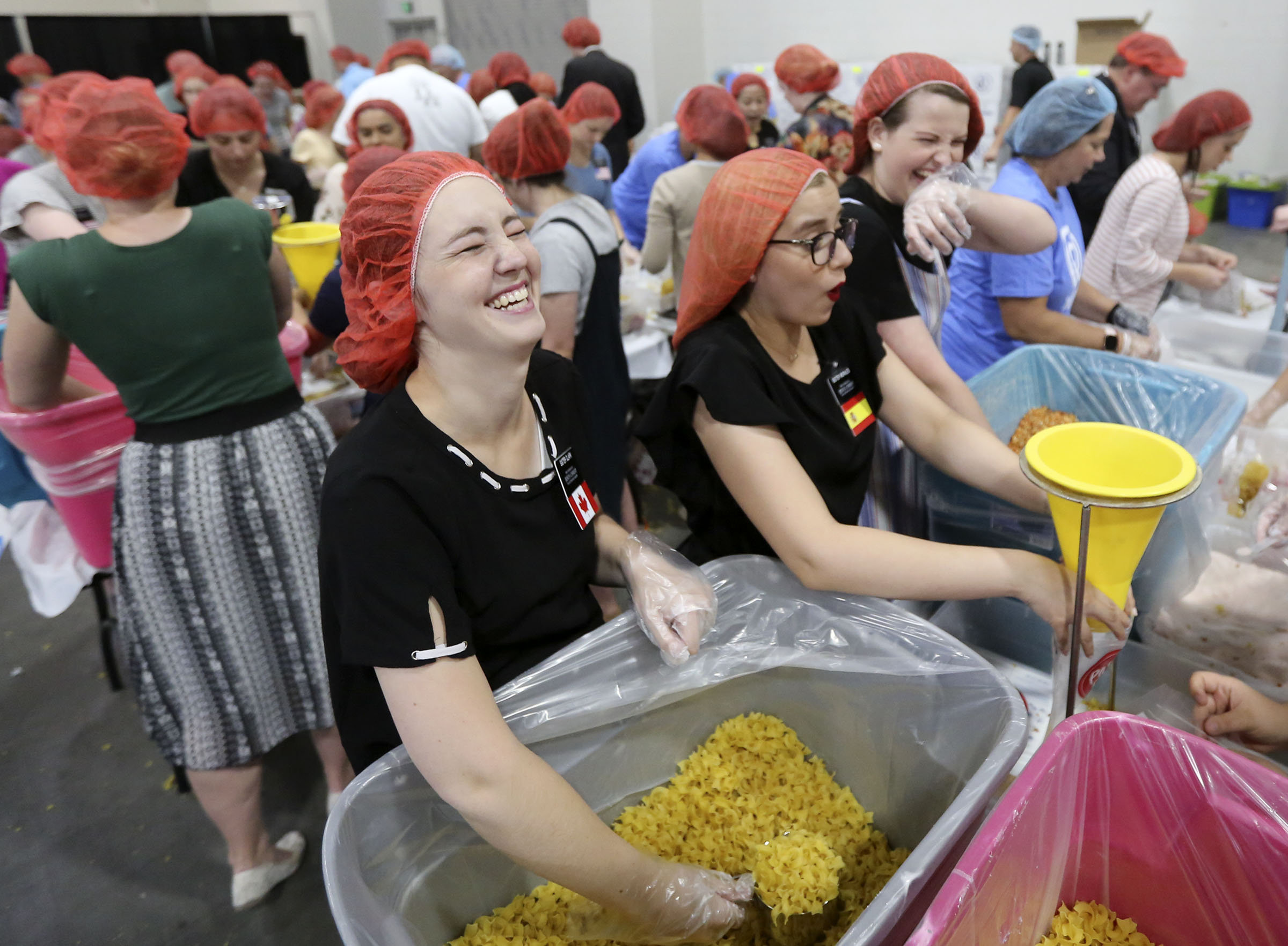 Sister Zoey Clark, Sister Priscilla Morales and Sister Callie Jorgensen — missionaries from Temple Square — package pasta dinners for a service project during the 68th United Nations Civil Society Conference at the Salt Palace Convention Center in Salt Lake City on Monday, Aug. 26, 2019.