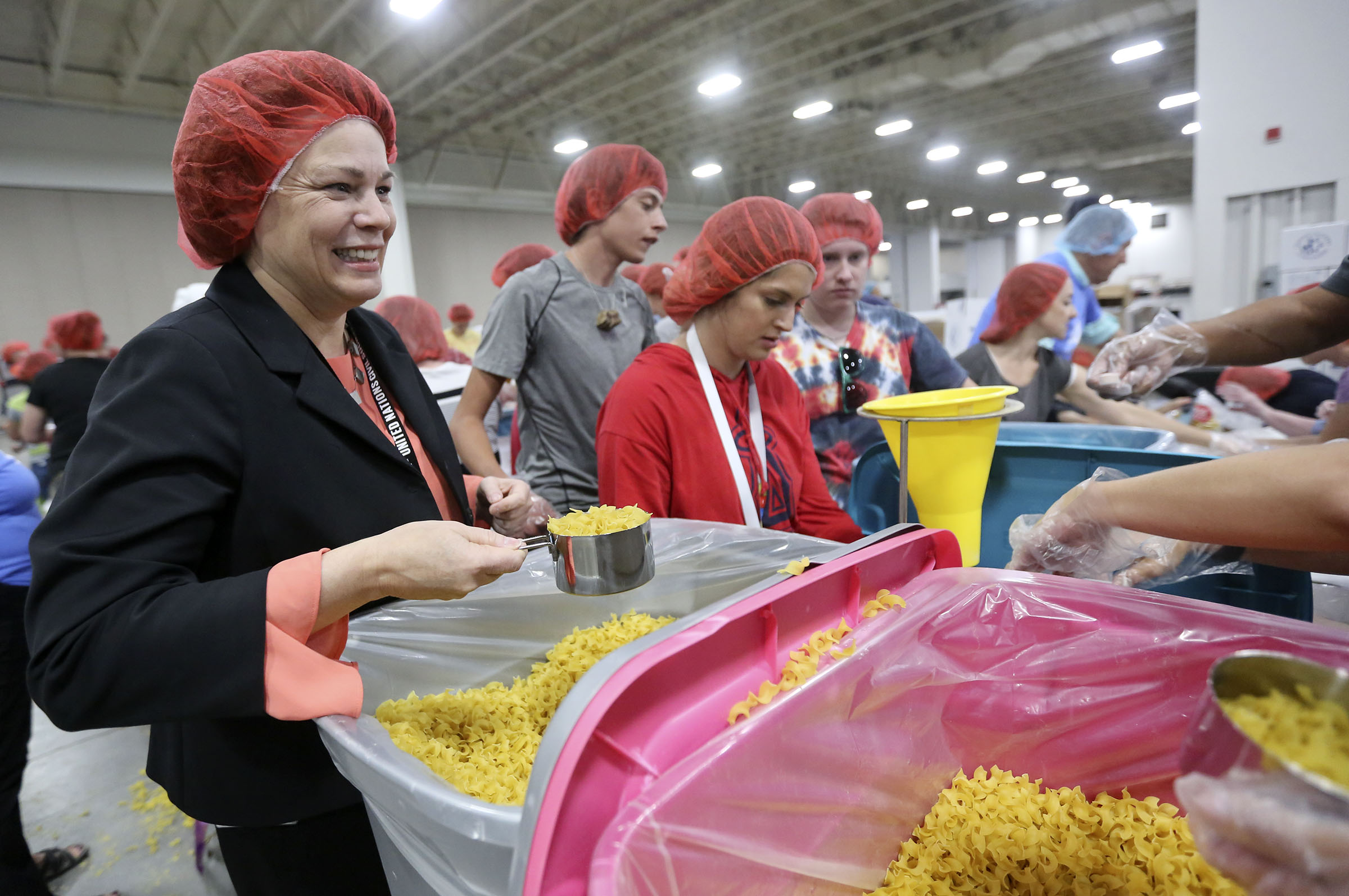 Sister Sharon Eubank, first counselor in the Church of Jesus Christ of Latter-day Saints Relief Society general presidency, packages pasta dinners for a service project during the 68th United Nations Civil Society Conference at the Salt Palace Convention Center in Salt Lake City on Monday, Aug. 26, 2019.