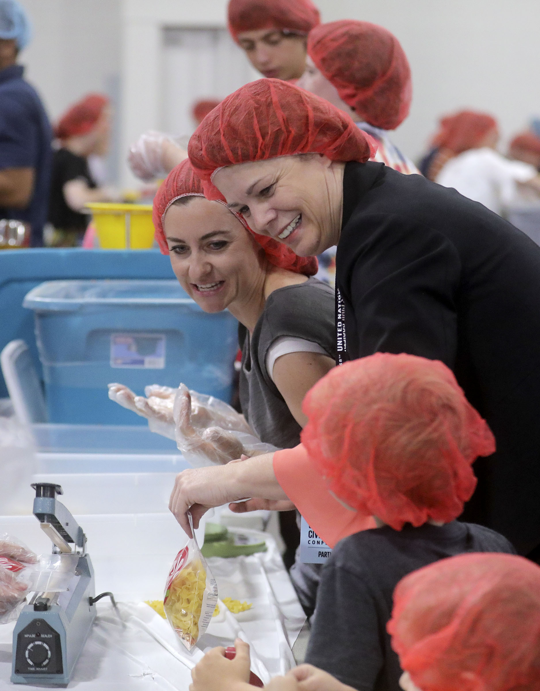 Bri Adams and Sister Sharon Eubank, first counselor in the Church of Jesus Christ of Latter-day Saints Relief Society general presidency, package pasta dinners for a service project during the 68th United Nations Civil Society Conference at the Salt Palace Convention Center in Salt Lake City on Monday, Aug. 26, 2019.