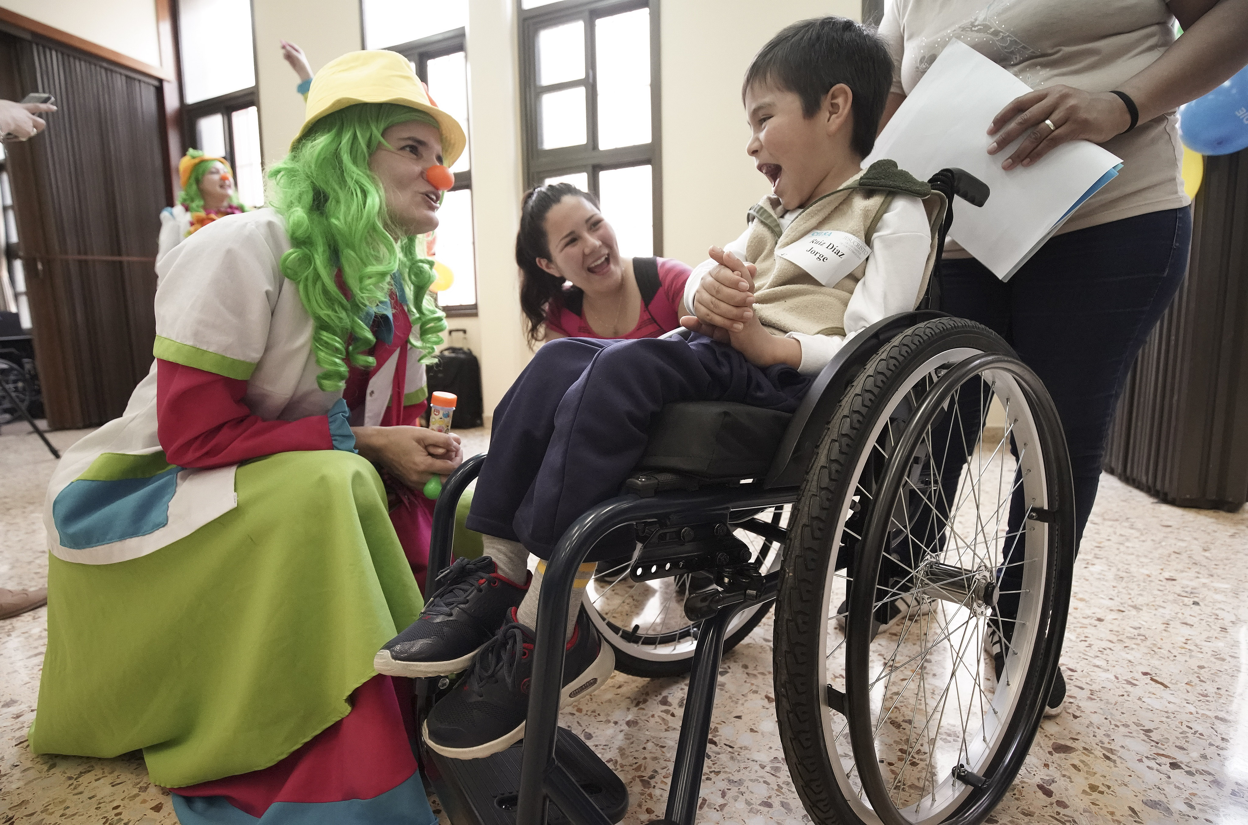 Jorge Diaz is entertained as Latter-day Saint Charities donated wheelchairs to recipients at the Villa Urquiza Ward meetinghouse in Buenos Aires, Argentina, on Wednesday, Aug. 28, 2019.