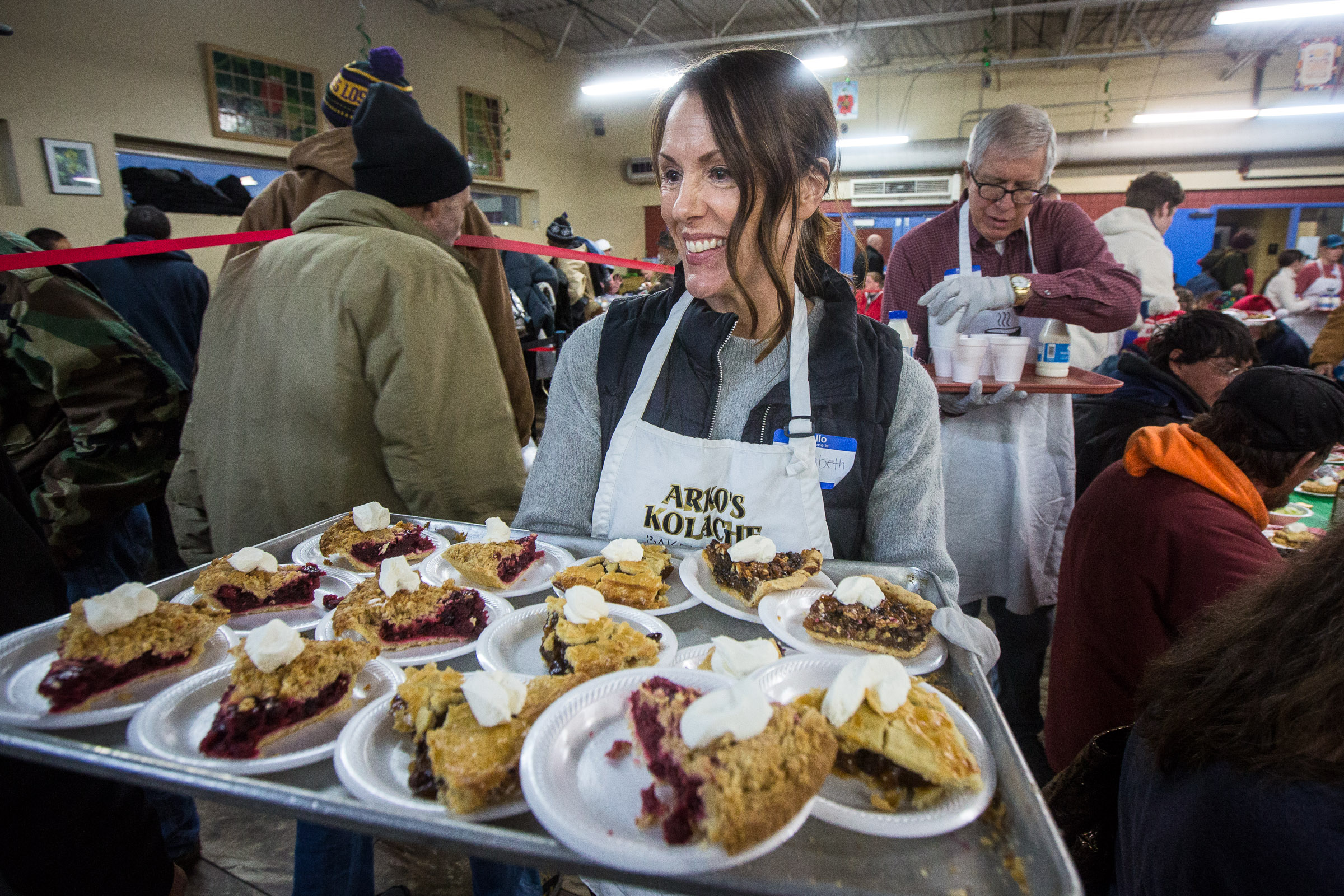 Elizabeth Weiler serves up pies as Pamela Atkinson and other community leaders serve the annual Christmas dinner to more than 800 homeless Utahns at St. Vincent de Paul Dining Hall in Salt Lake City on Tuesday, Dec. 25, 2018.