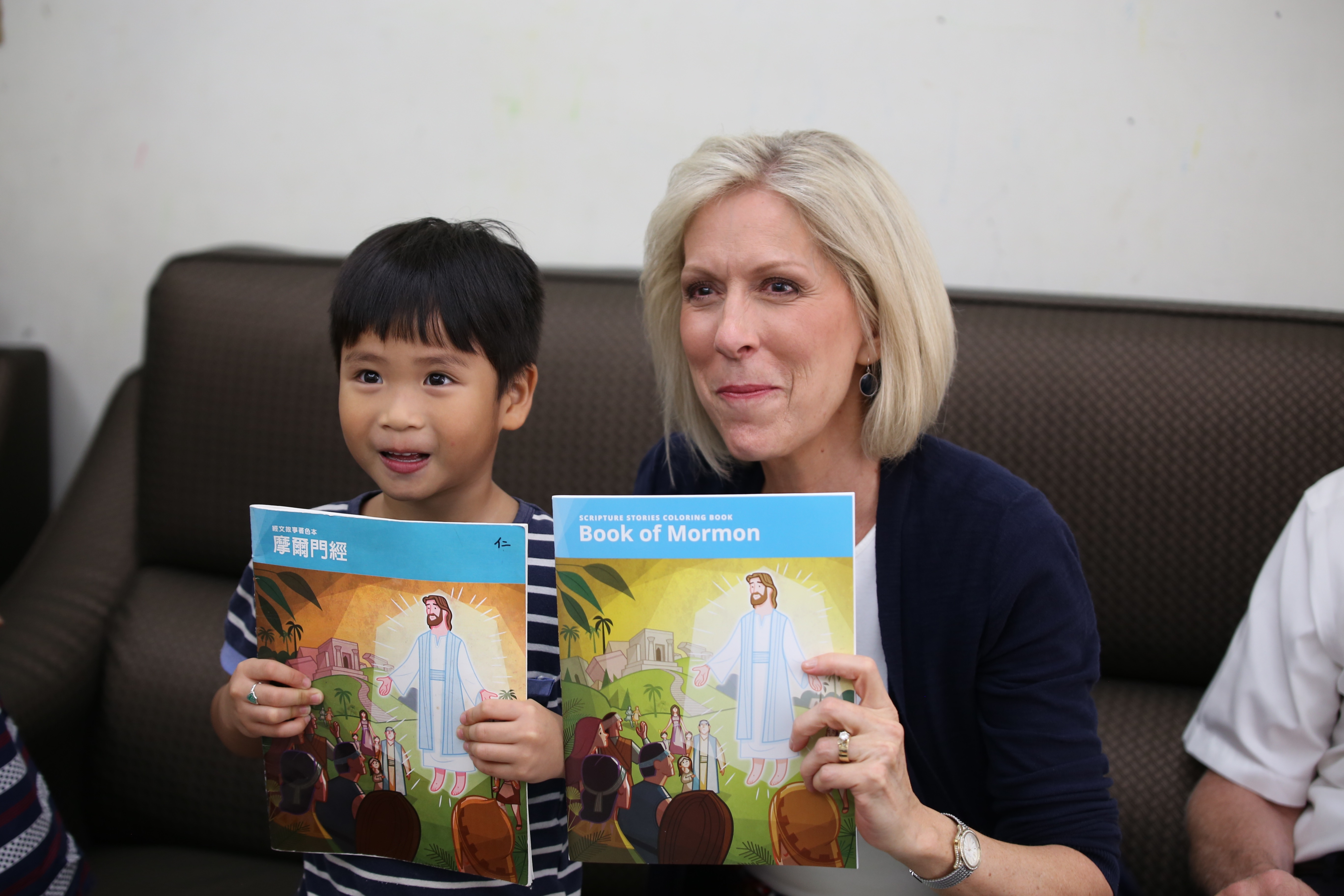 Sister Joy D. Jones, Primary general president, and a young boy show off their matching Book of Mormon coloring books during a visit to a member family's home in Taitung, Taiwan, during a visit to the Asia Area from Aug. 17 to 14, 2019.