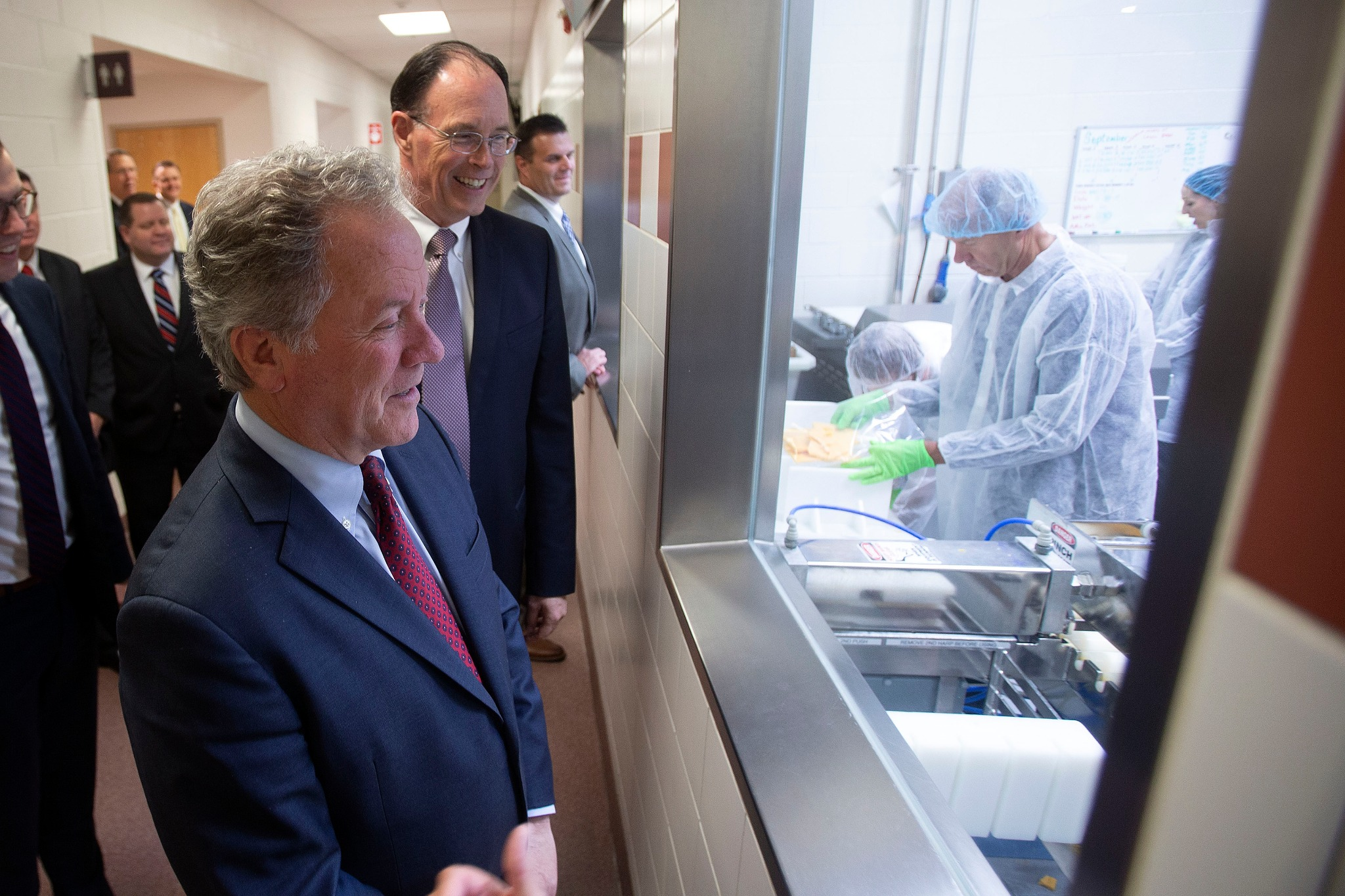 David Beasley, executive director of the United Nations World Food Programme, watches through a window in the dairy section of Welfare Square how cheese and other items are made during a tour on Monday, Sept. 30, 2019.