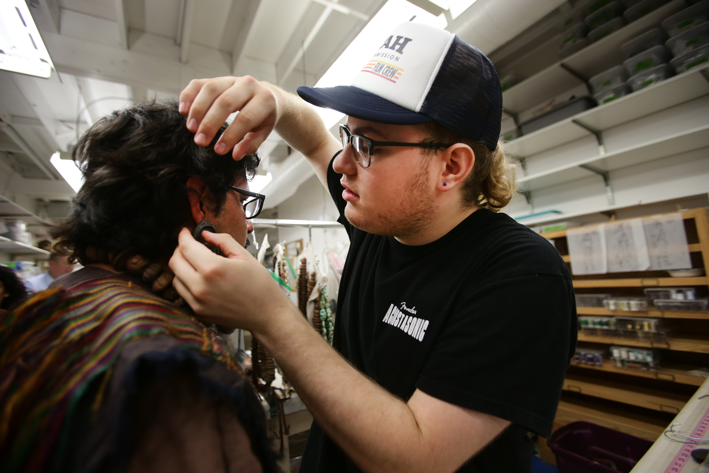 Ivan Amezquita gets ear-rings from Mason Creer in the costume room as work on production of the Book of Mormon videos continues in Provo, Utah, at the Motion Picture Studio on Tuesday, Sept. 3, 2019.