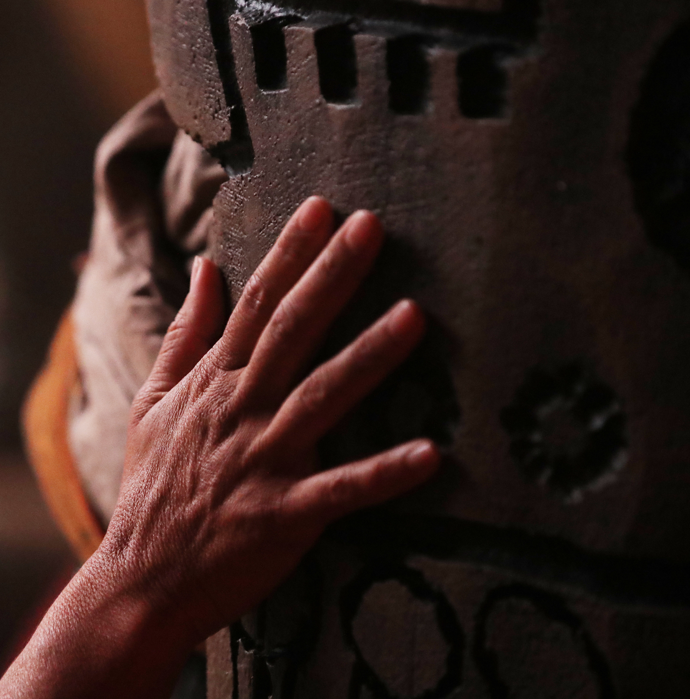 A cast member places her hand on a column in King Noah's court during filming of the Book of Mormon video series in Provo, Utah, at the Motion Picture Studio on Tuesday, Sept. 3, 2019.