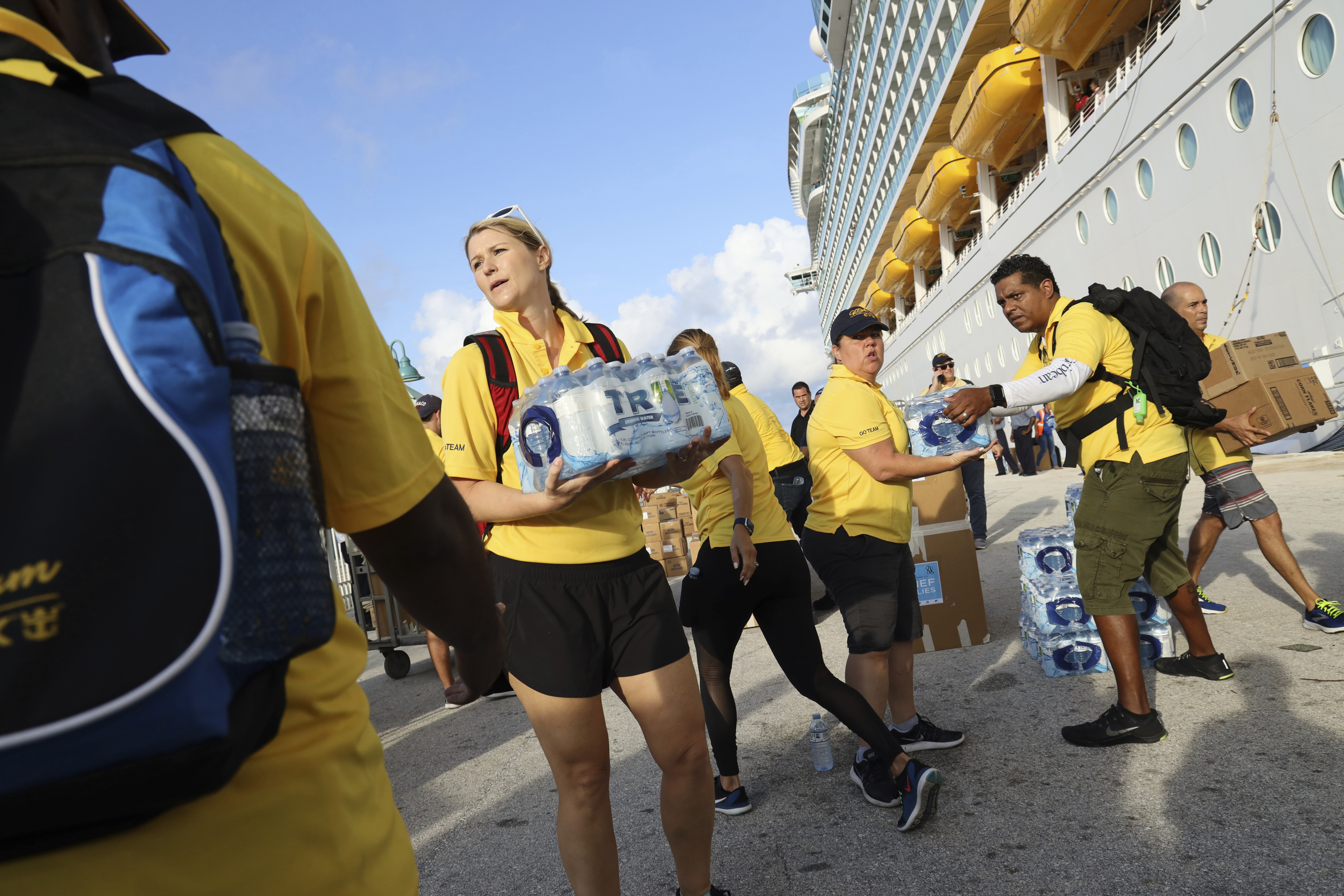 Volunteers from the Royal Caribbean's Go Team load water and relief supplies on to trucks on the quayside of Freeport Harbour in Grand Bahama, Bahamas, Sunday, Sept. 8, 2019, in the wake of Hurricane Dorian. Electricity remains down in Grand Bahama and there is still no running water one week after the storm hit. (AP Photo/Tim Aylen)