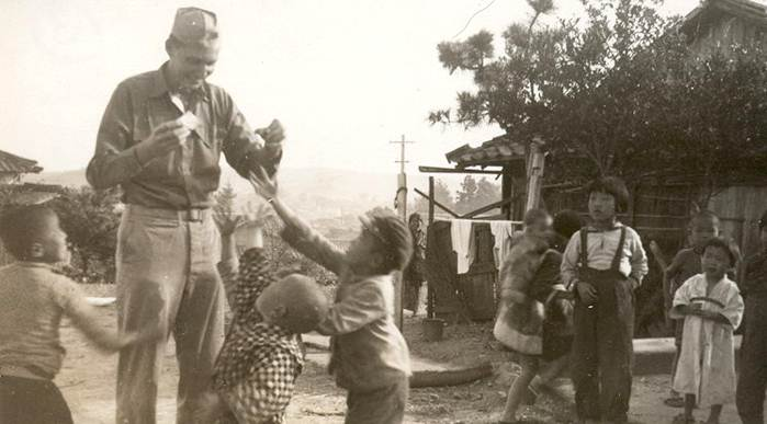 L. Tom Perry is pictured with Japanese children. While in Nagasaki, Elder Perry and other Marines not only helped rebuild churches, but helped local clergy organize orphanages for displaced children.