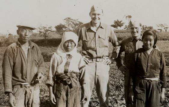 L. Tom Perry, center, is pictured with Japanese friends and a fellow Marine.