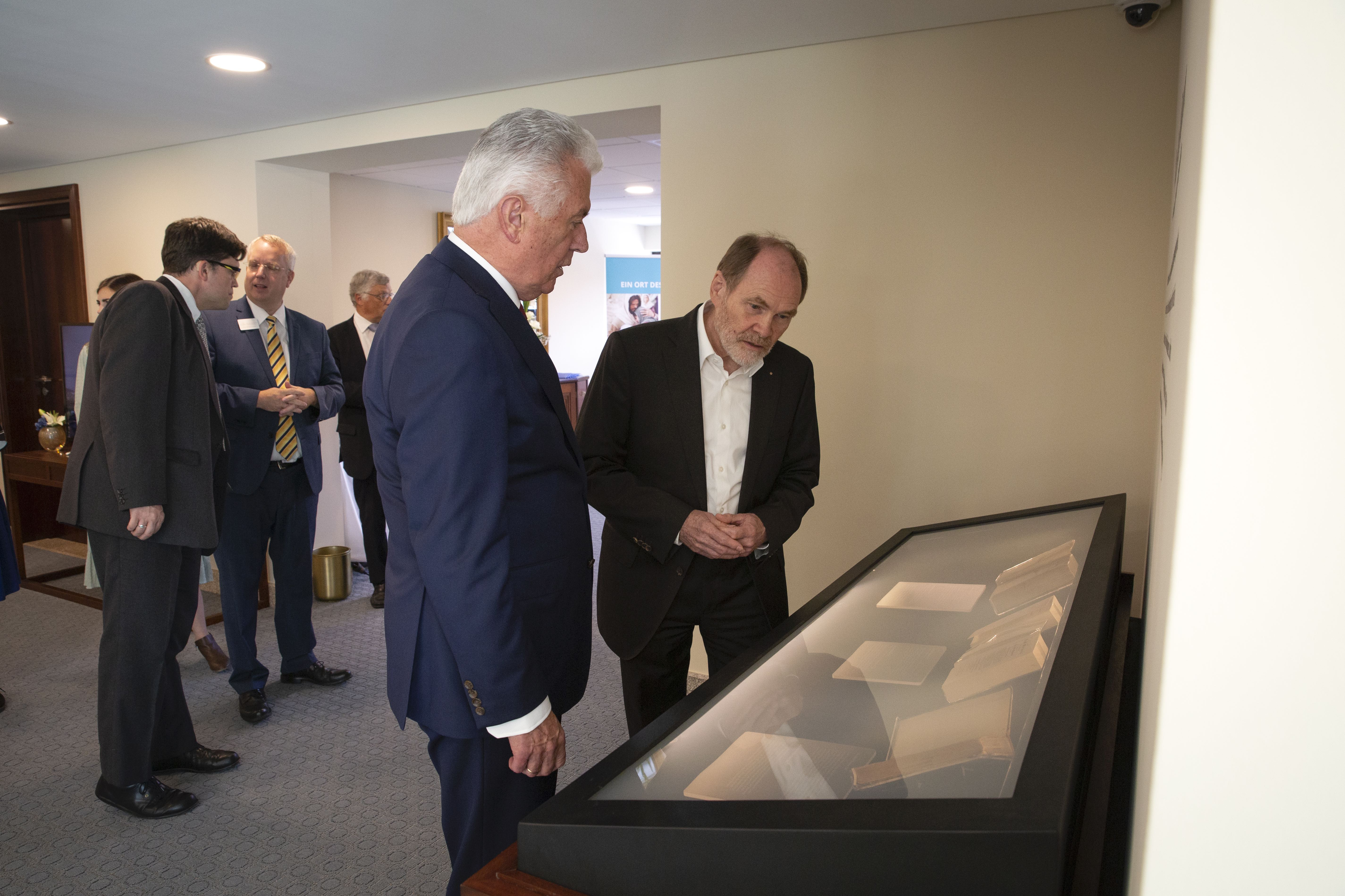 Elder Dieter F. Uchtdorf, left, shows Wolfgang Thielman — a journalist from Die Zeit, a major, German newspaper — a case displaying four early copies of the Book of Mormon in German and English at the Frankfurt Temple Visitors' Center in Friedrichsdorf, Germany, on Tuesday, Sept. 10, 2019.