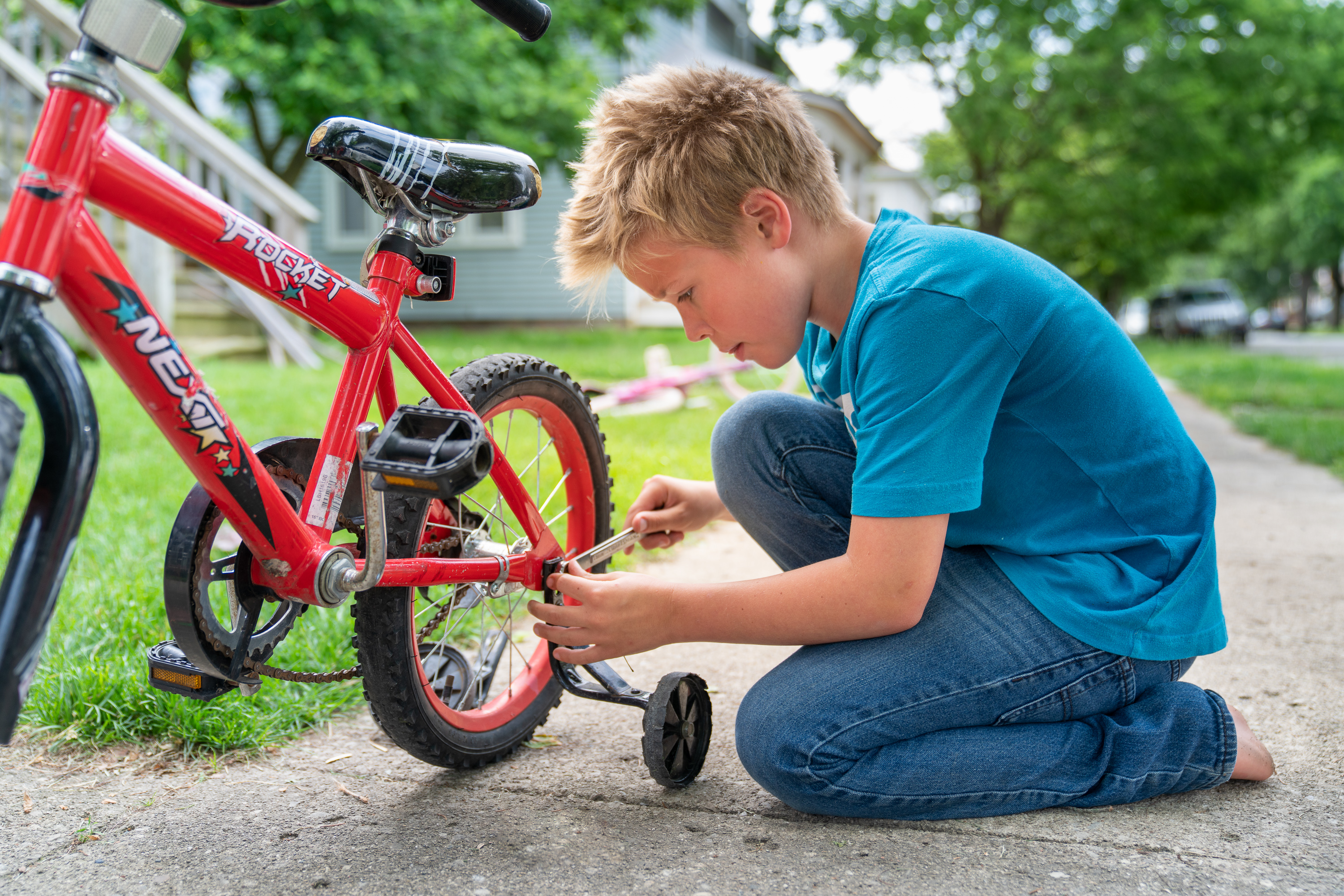 A young boy from a pilot stake in Columbus, Ohio works on his bicycle as part of the Children and Youth program.
