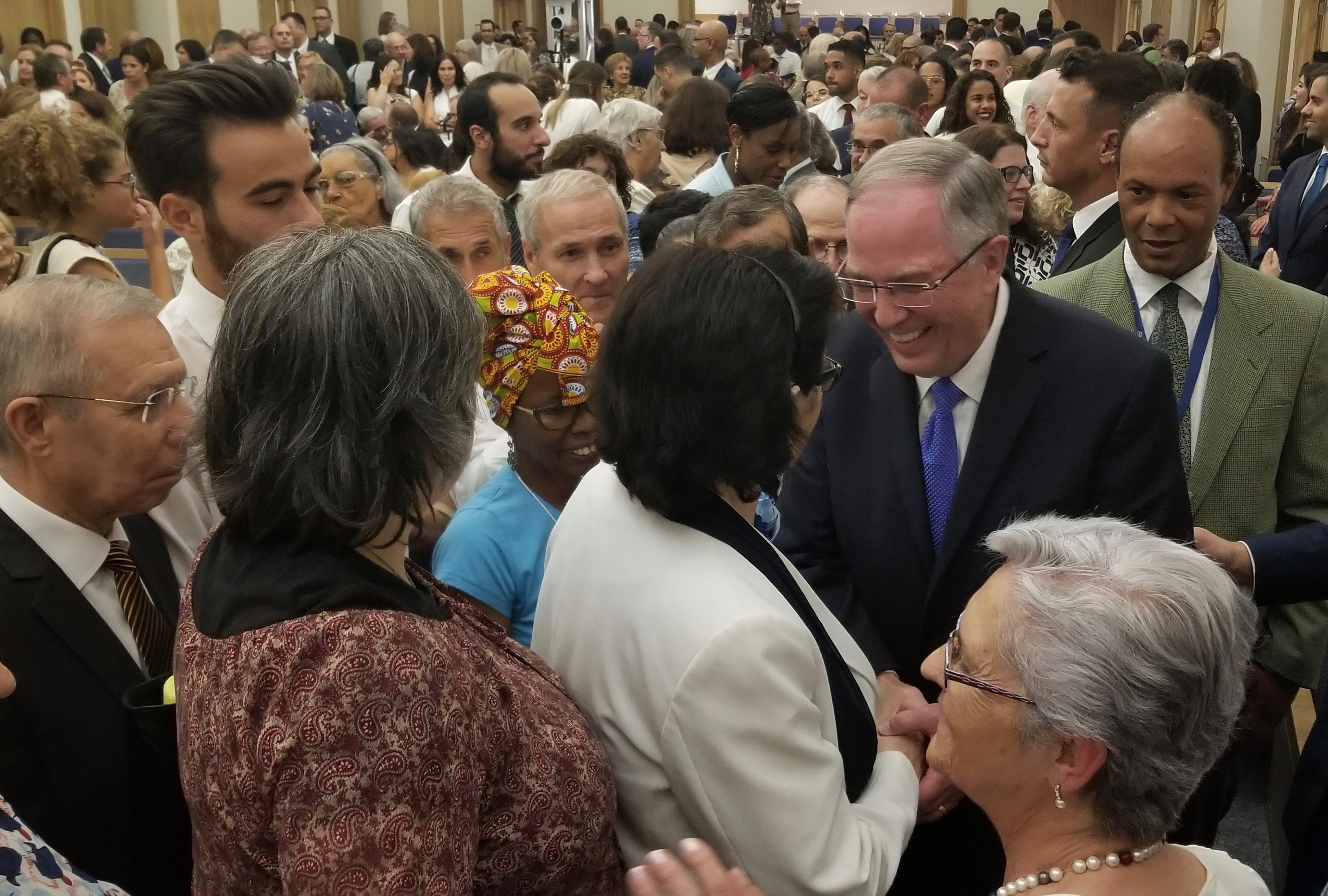Elder Neil L. Andersen of the Quorum of the Twelve Apostles, right, greets a member following a meeting with Portugal's pioneer Latter-day Saints on Saturday, Sept. 14, 2019, in Lisbon.
