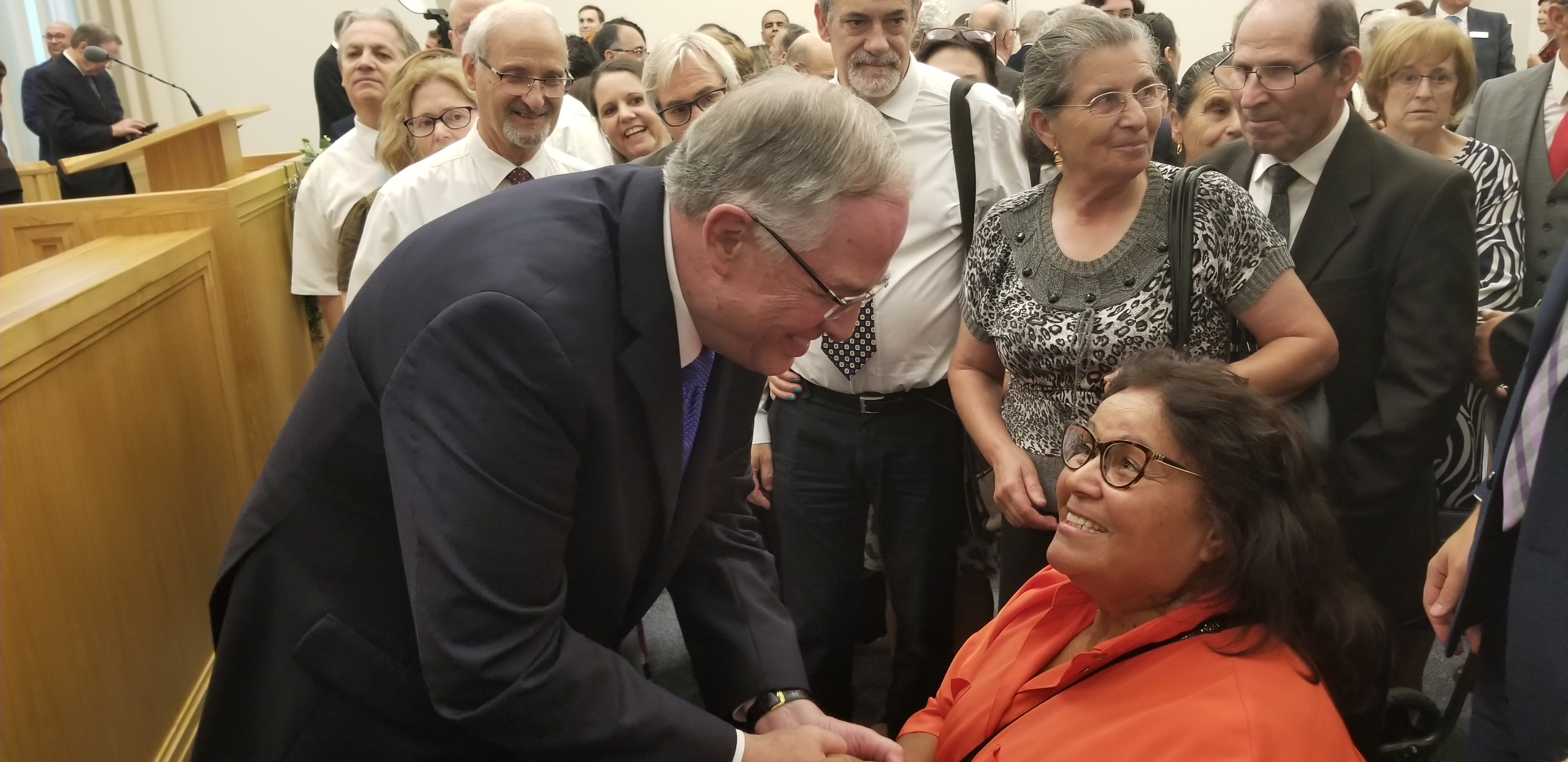 Elder Neil L. Andersen of the Quorum of the Twelve Apostles, right, greet individuals following a meeting with Portugal's pioneer Latter-day Saints on Saturday, Sept. 14, 2019, in Lisbon. The crowd of members in the meetinghouse chapel waiting to meet him is visible to his side and behind him.