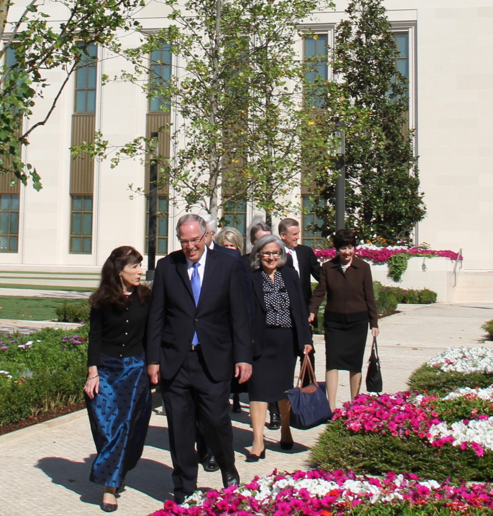 Elder Neil L. Andersen and Sister Kathy Andersen lead out in the courtyard following a walk-through of the Lisbon Portugal Temple on Saturday, Sept. 14, 2019. They are joined by Elder José A. Teixeira, Sister Filomena Teixeira, Elder Gary B. Sabin, Sister Valerie Sabin, Elder Kevin R. Duncan and Sister Nancy Duncan.