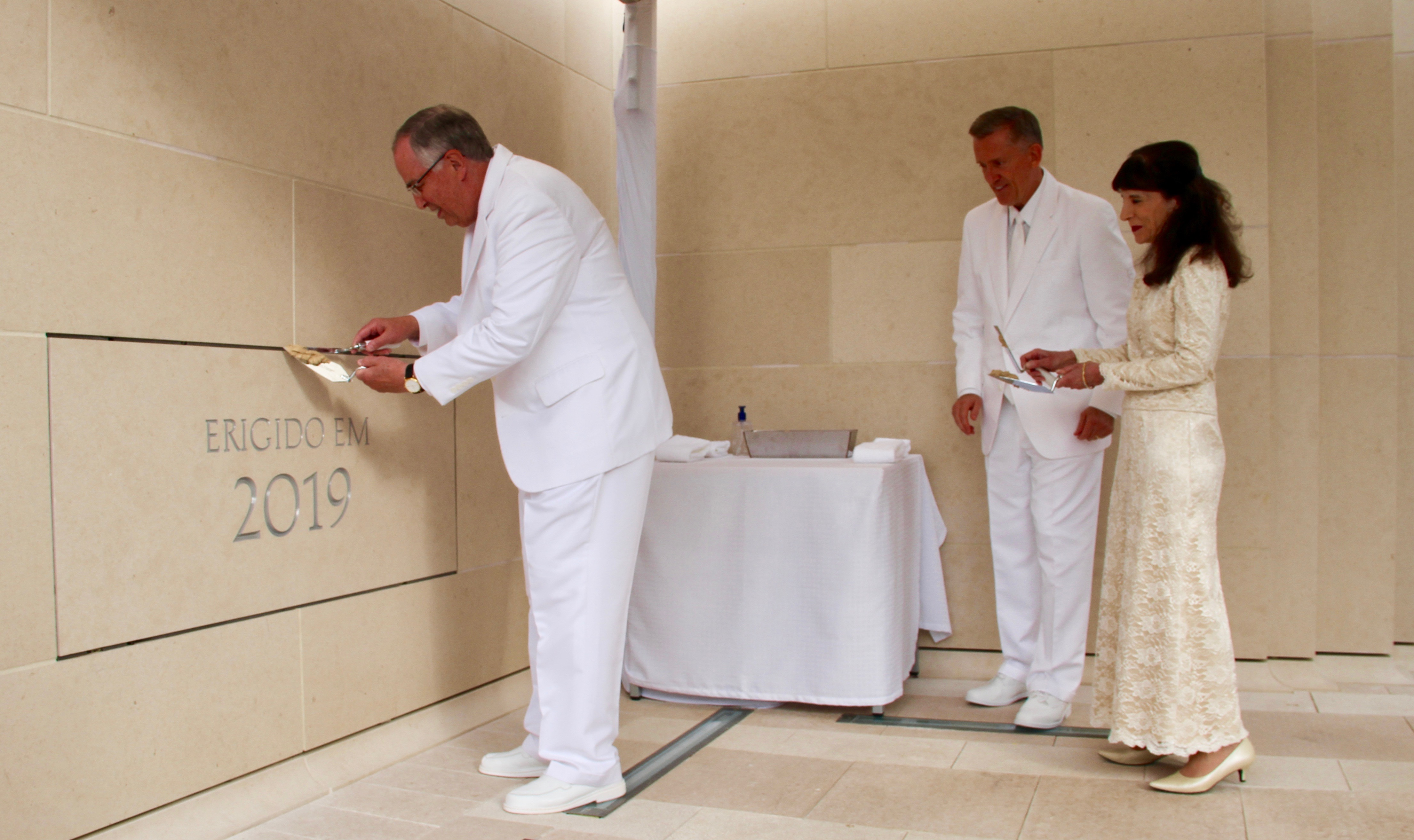 Elder Neil L. Andersen of the Quorum of the Twelve Apostles applies mortar around the cornerstone of the Lisbon Portugal Temple dedication on Sunday, Sept. 15, 2019. He is joined by his wife, Sister Kathy Andersen, right, and Elder Kevin R. Duncan, middle.