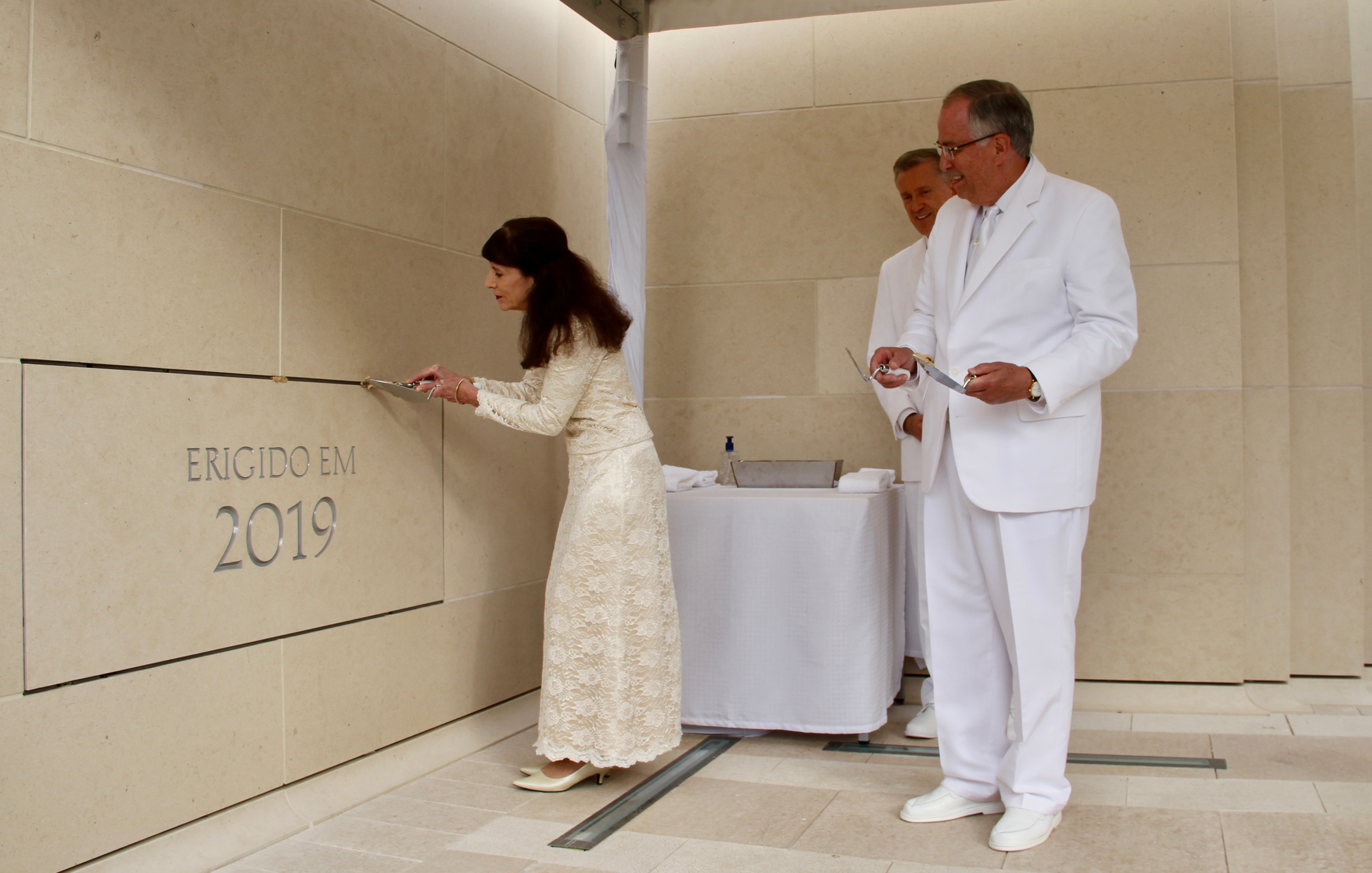 Sister Kathy Andersen applies mortar around the cornerstone of the Lisbon Portugal Temple dedication on Sunday, Sept. 15, 2019, being watched by her husband, Elder Neil L. Andersen of the Quorum of the Twelve Apostles, right, and Elder Kevin R. Duncan, behind.