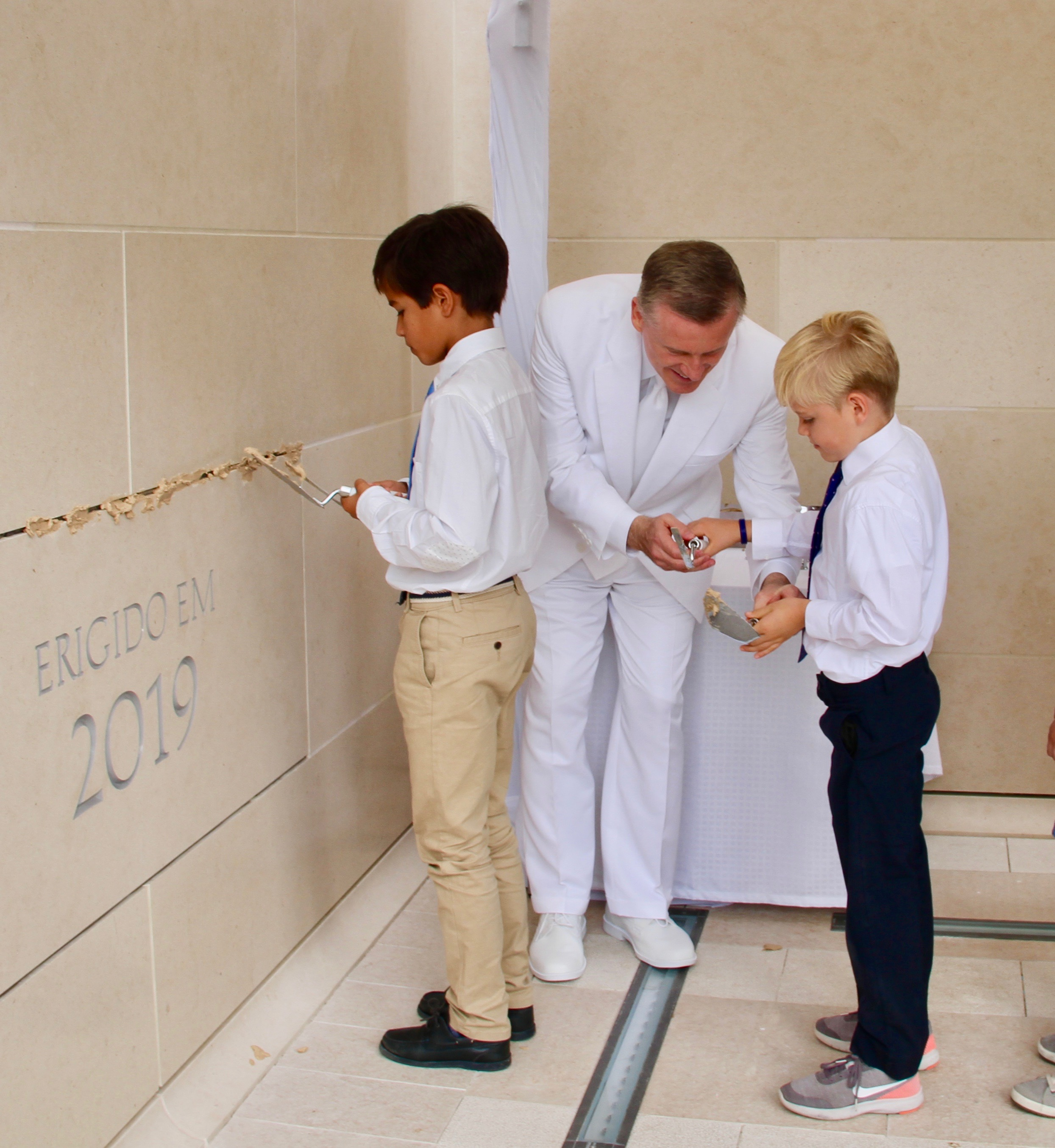Elder Kevin R. Duncan helps young boys who were invited to participate in the cornerstone ceremony of the Lisbon Portugal Temple dedication on Sunday, Sept. 15, 2019.
