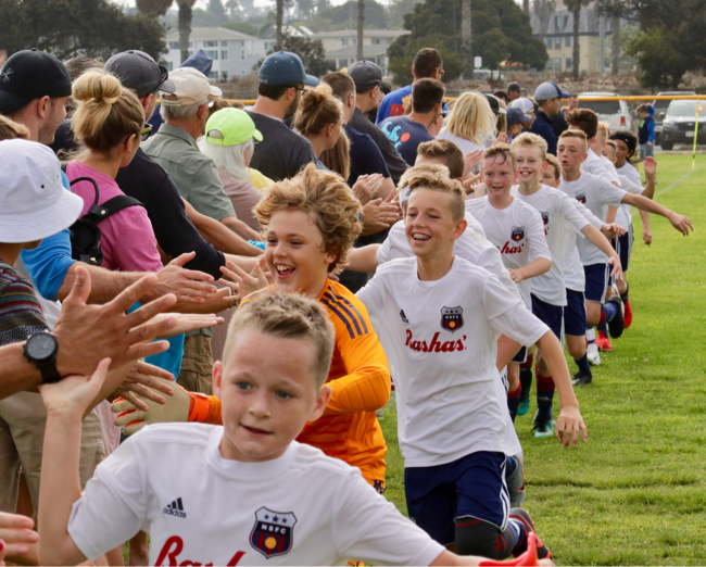 The 2007 Boys Blue soccer team coached by Todd Walden high-fives parents after the La Jolla tournament in September 2019.