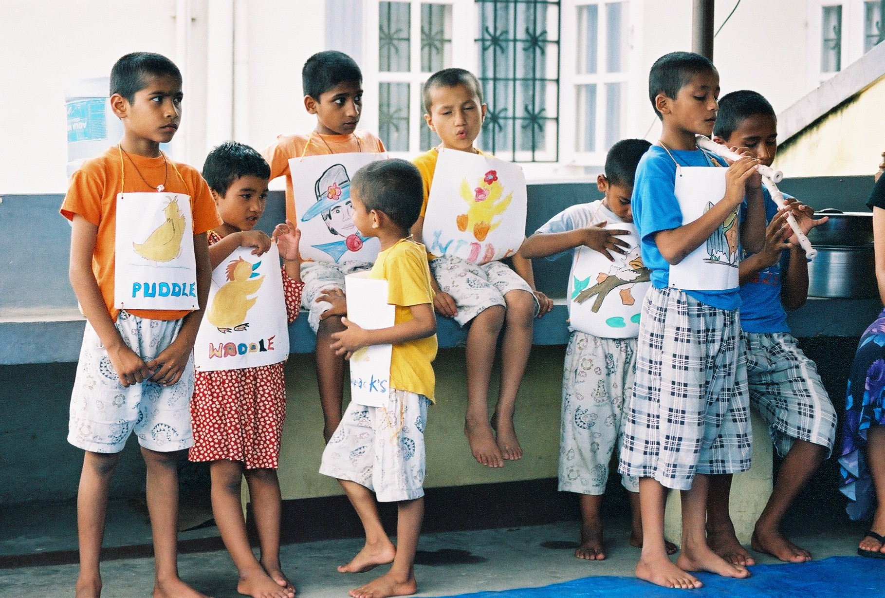 Children from Home of Hope in Kathmandu, Nepal gather to share drawings they made during an activity time in 2005.