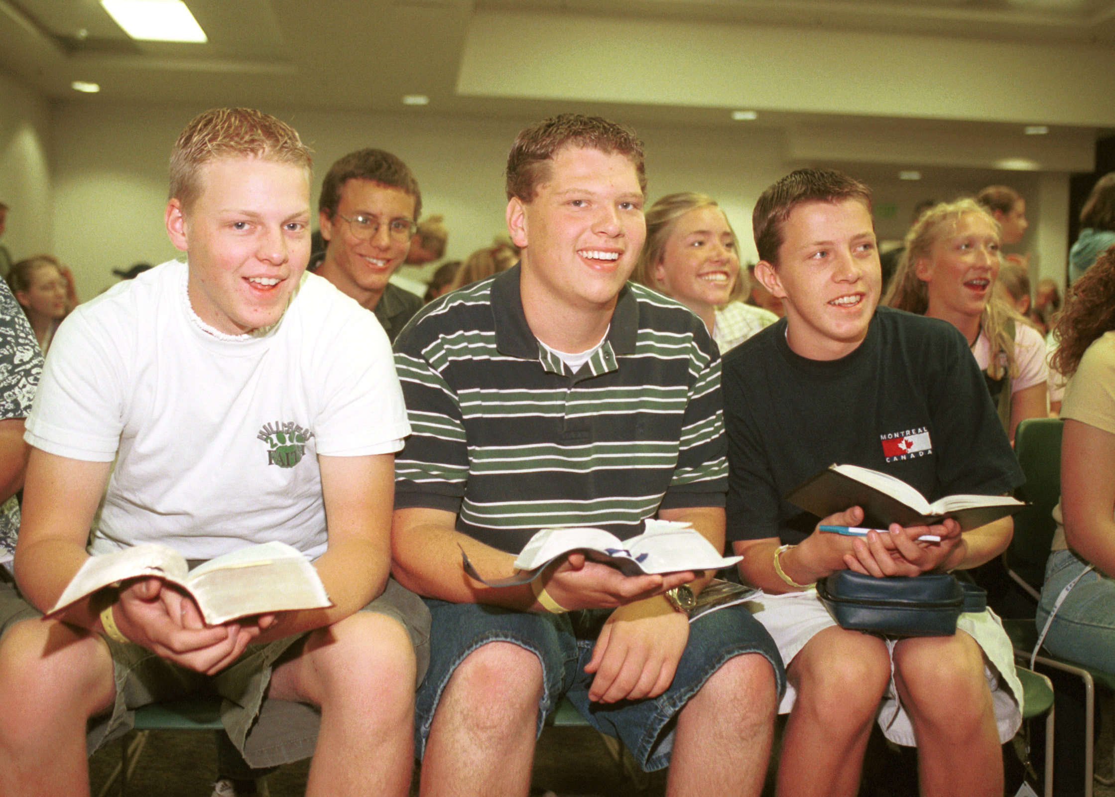 Young men sit with their scriptures open during a class at Especially for Youth.