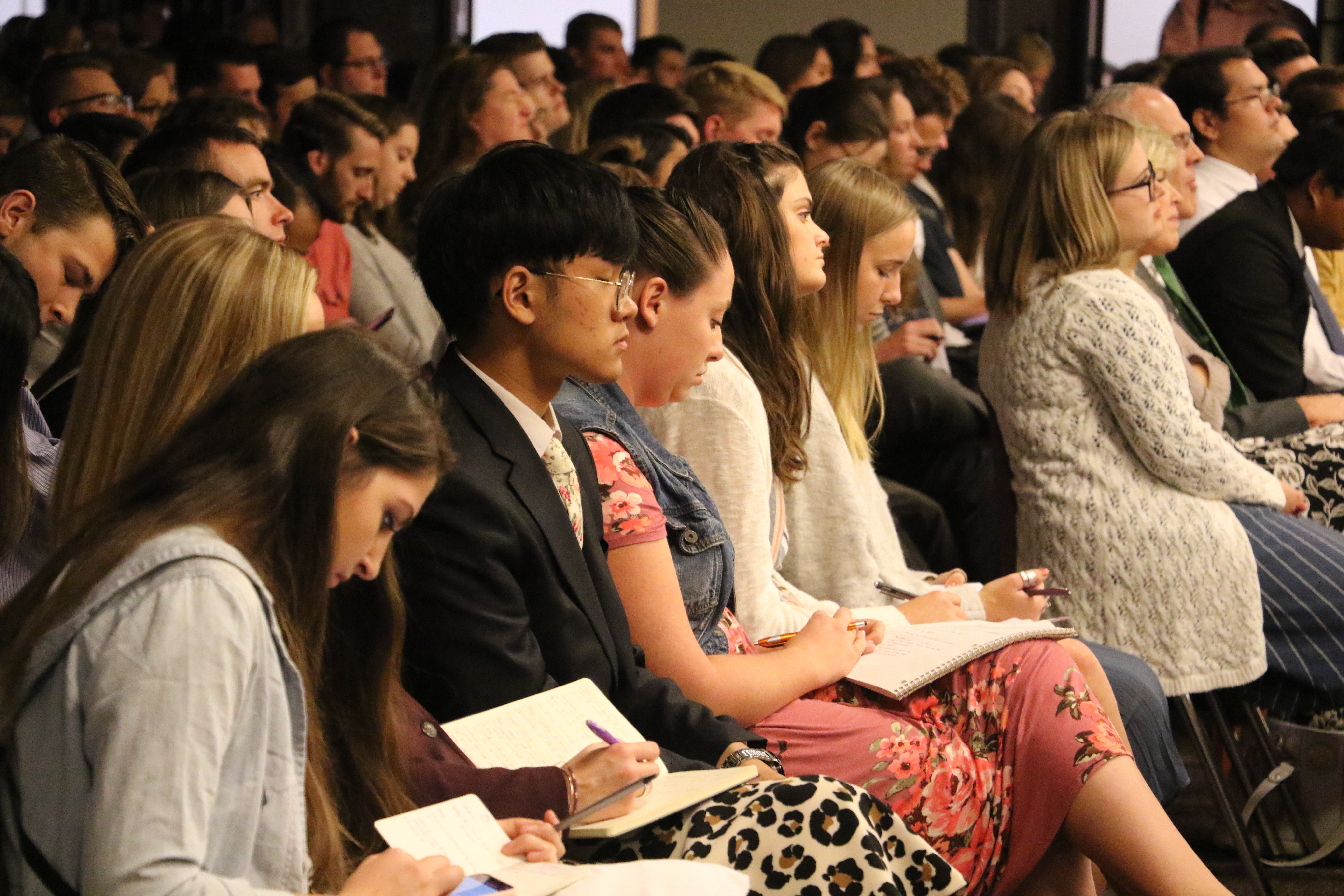 Students in the audience take notes and listen at a devotional with President M. Russell Ballard on the UVU campus in Orem, Utah on Friday, Sept. 20, 2019.