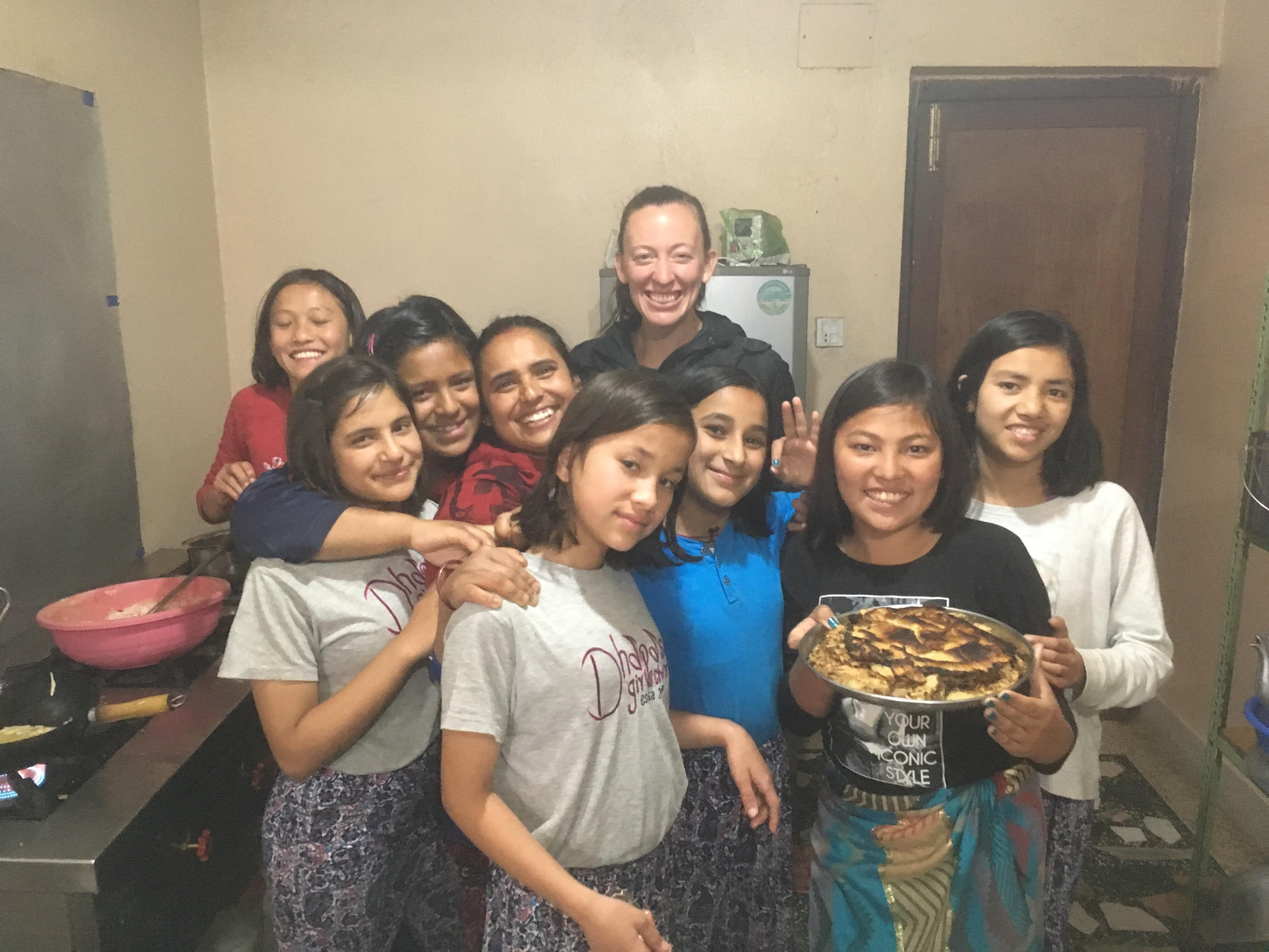 Self Help Nepal volunteer Dani Edgar with some of the children from Home of Hope in Kathmandu, Nepal after cooking some food together at their home.