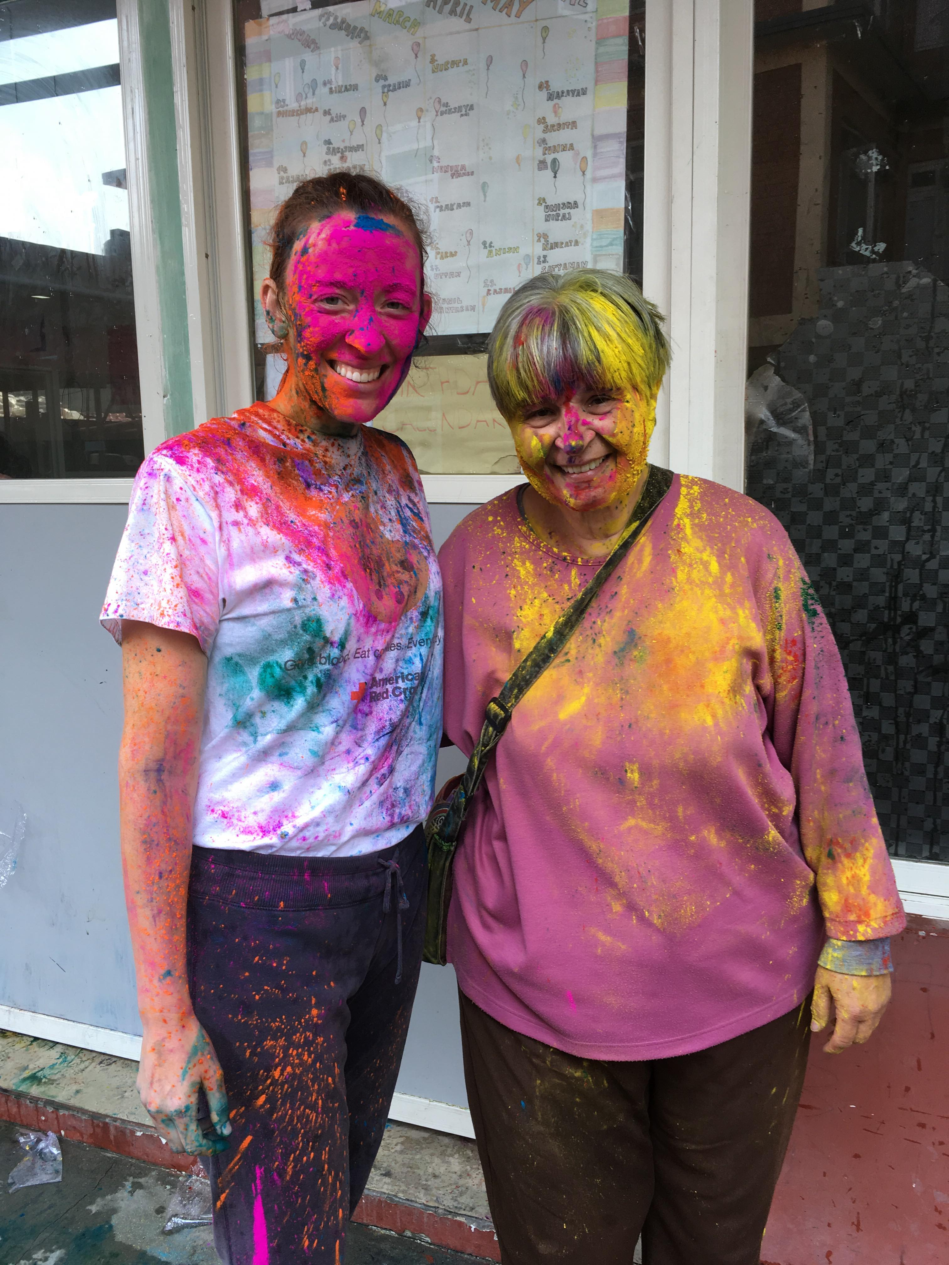 Ellen Dietrich, left, along with Self Help Nepal volunteer Dani Edgar, pose for a photo while covered in color dust following a Nepalese celebration at Home of Hope in Kathmandu, Nepal.