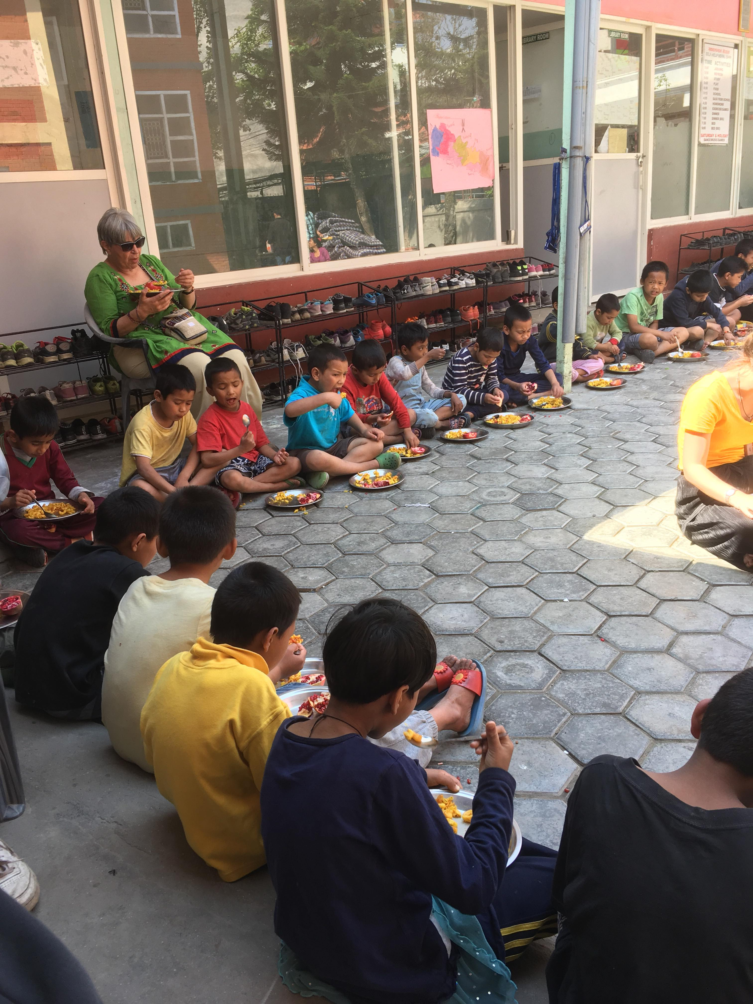 Children at Home of Hope in Kathmandu sit and eat a meal in the courtyard at their home in Kathmandu. Home of Hope or Self Help Nepal is a charity organization and children's home founded by Ellen Dietrich.
