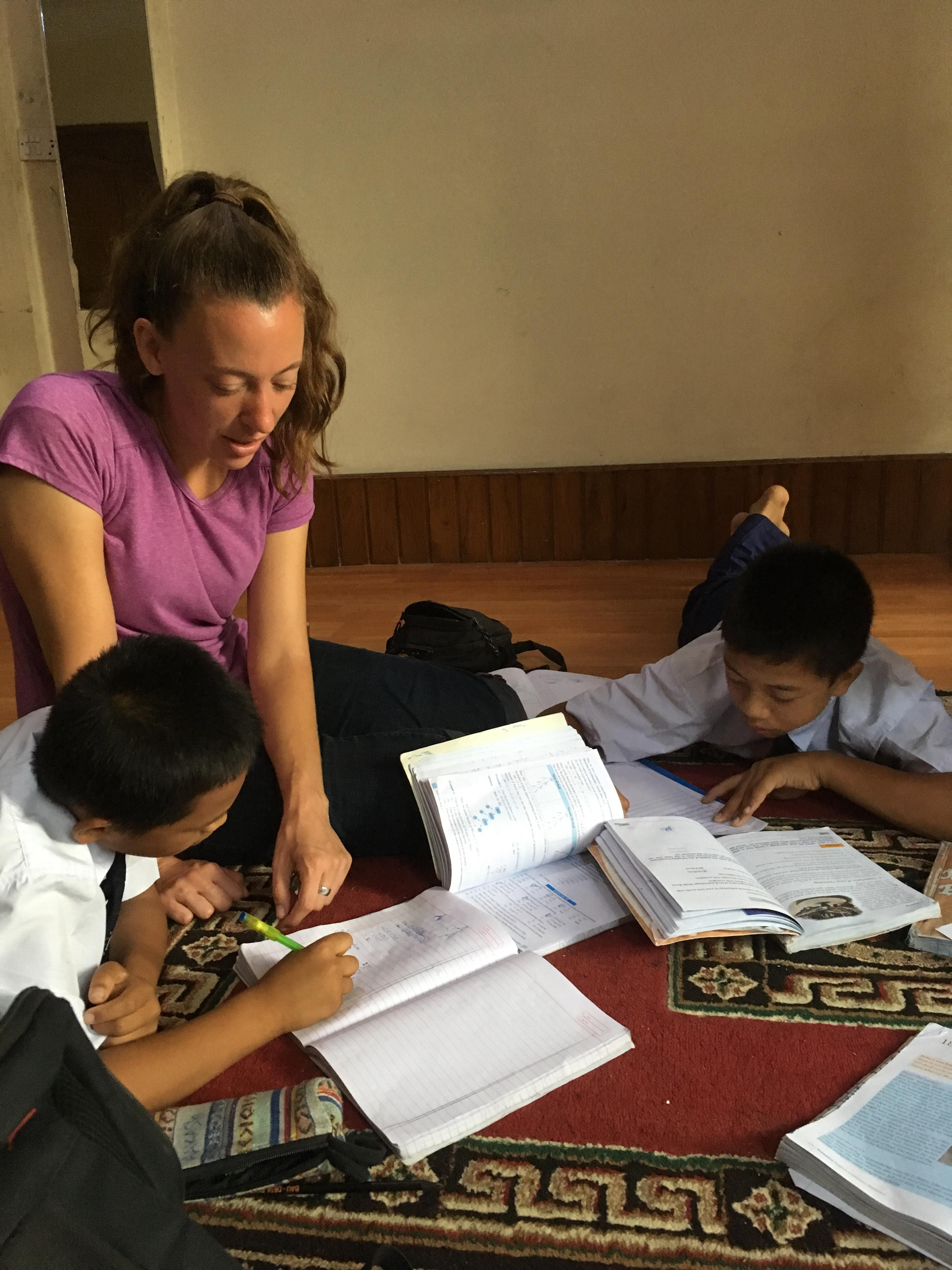 Dani Edgar, a volunteer with Self Help Nepal, helps children at Home of Hope — Nepal with their homework.