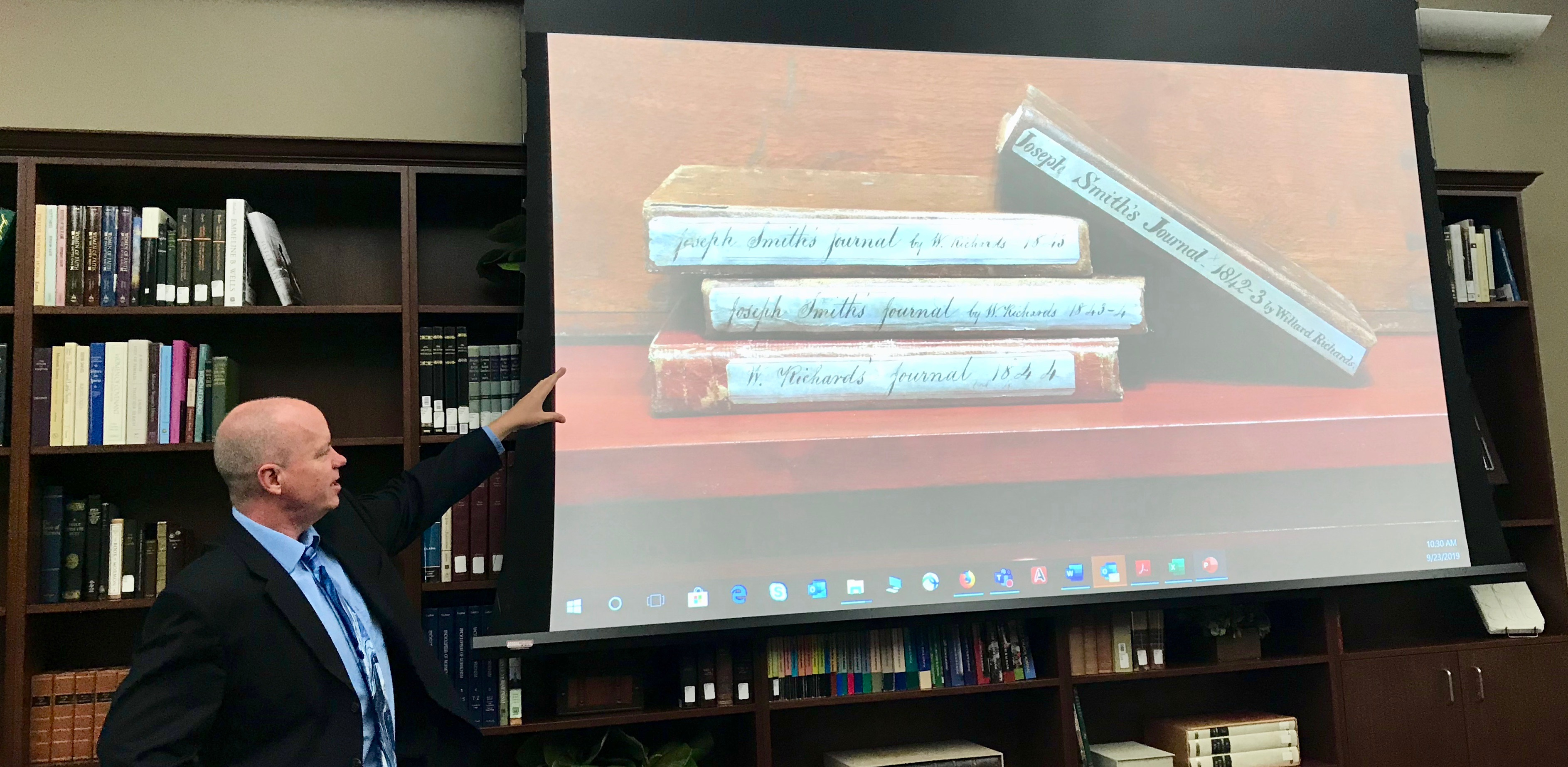 "Alex D. Smith, an editor with the Joseph Smith Papers project, points to a slide while discussing ""Documents, Vol. 9: December 1841-April 1842."""