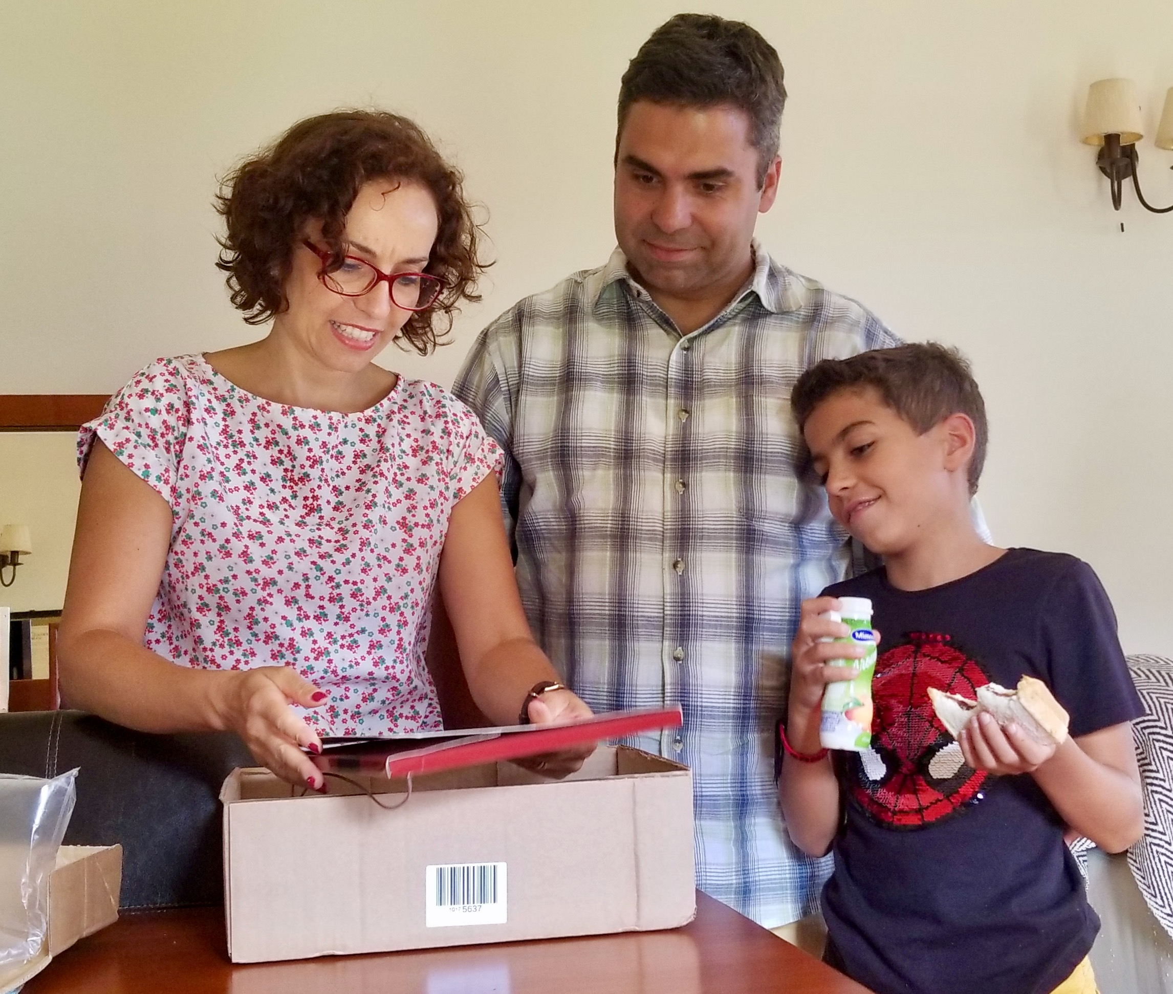 Tânia Alves, left, opens a box containing text books for her son, Samuel, right, while her husband, Paulo Alves, the Azores' district president, looks on in their home in São Mateus da Calheta, Terceira Island, on Sept. 16, 2019.​