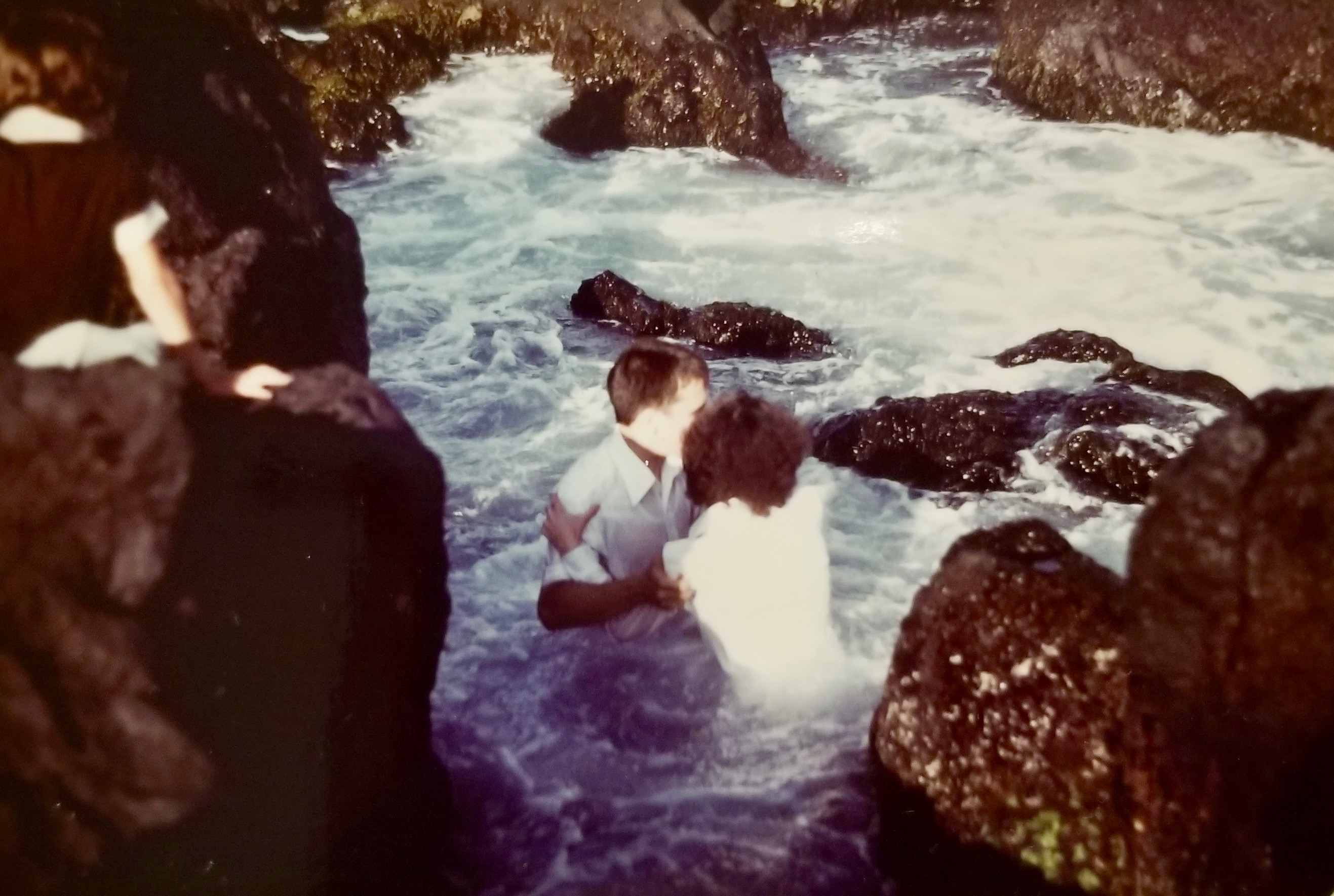 A photo showing the baptism of Alexandra Camacho Rodrigues, at age 18 on June 14, 1980, among the rocks and surf of the Azores' São Miguel Island.