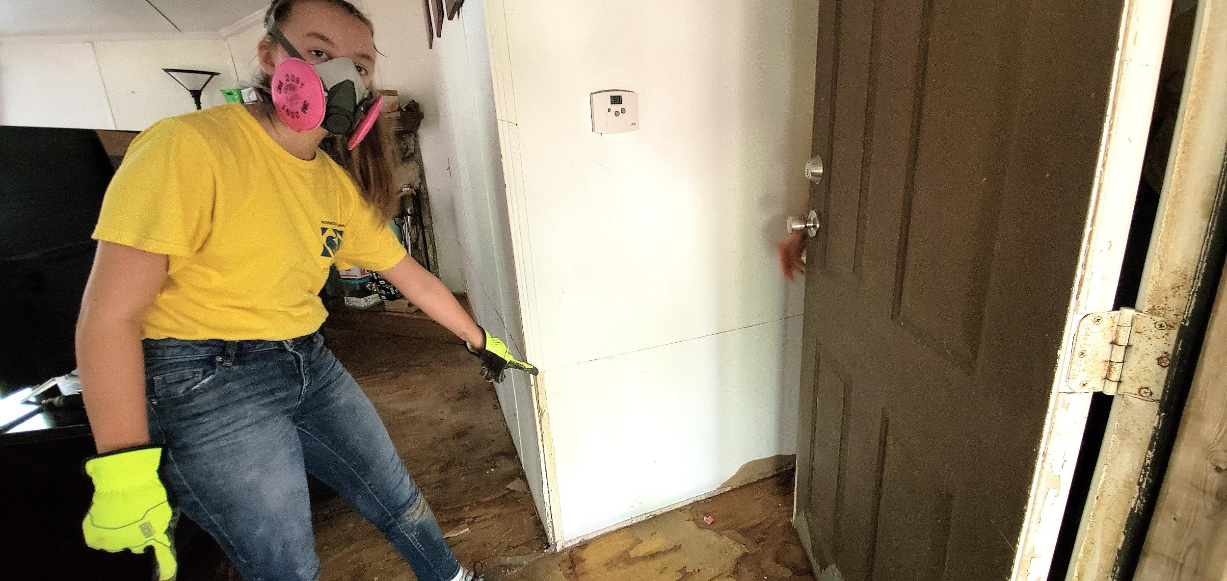 Elizabeth Mangum helps with cleanup in the home of Church member Fele Hernandez.