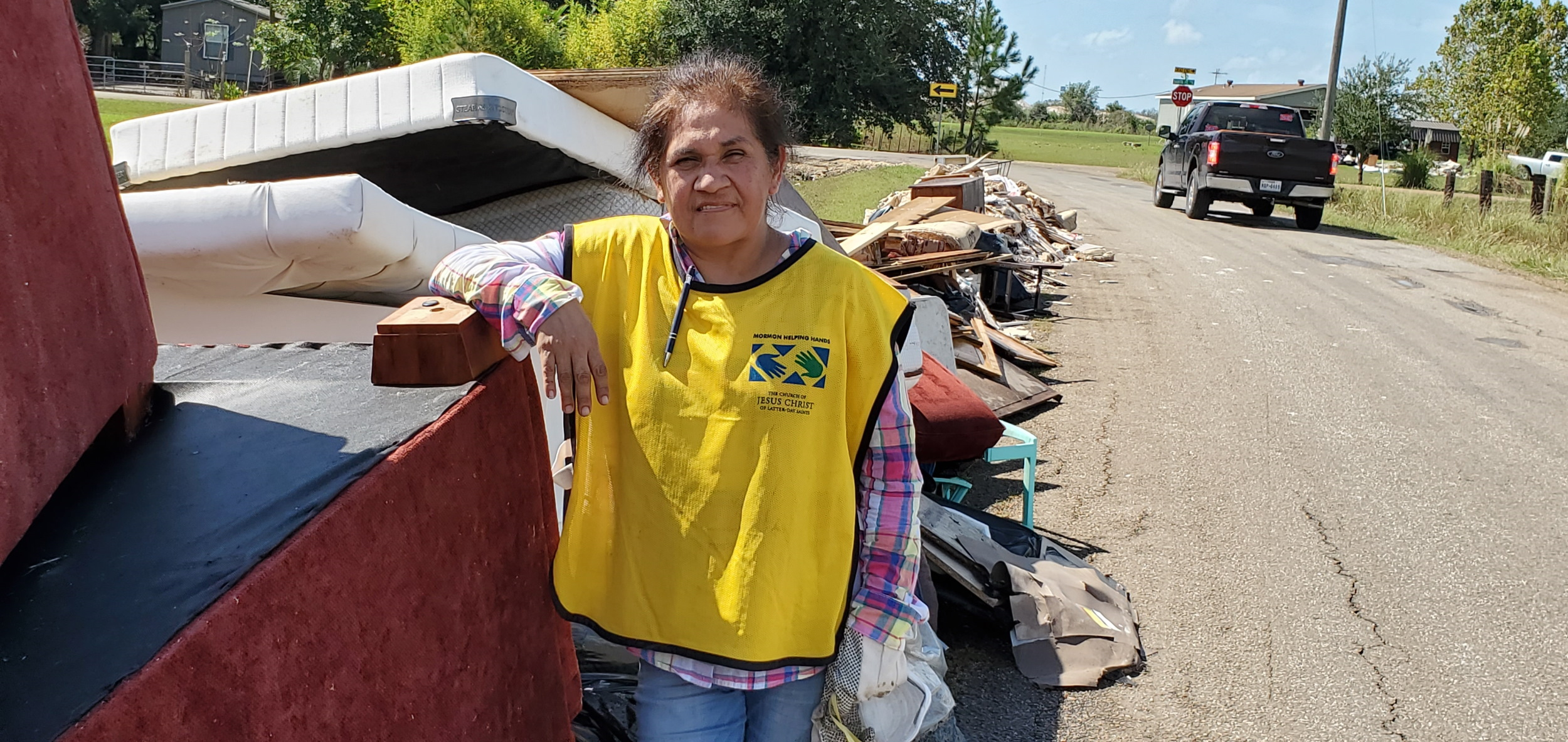 Elisa Zepeda whose home was flooded stands in front of the long pile of debris, her soaked home furnishing and interior walls.