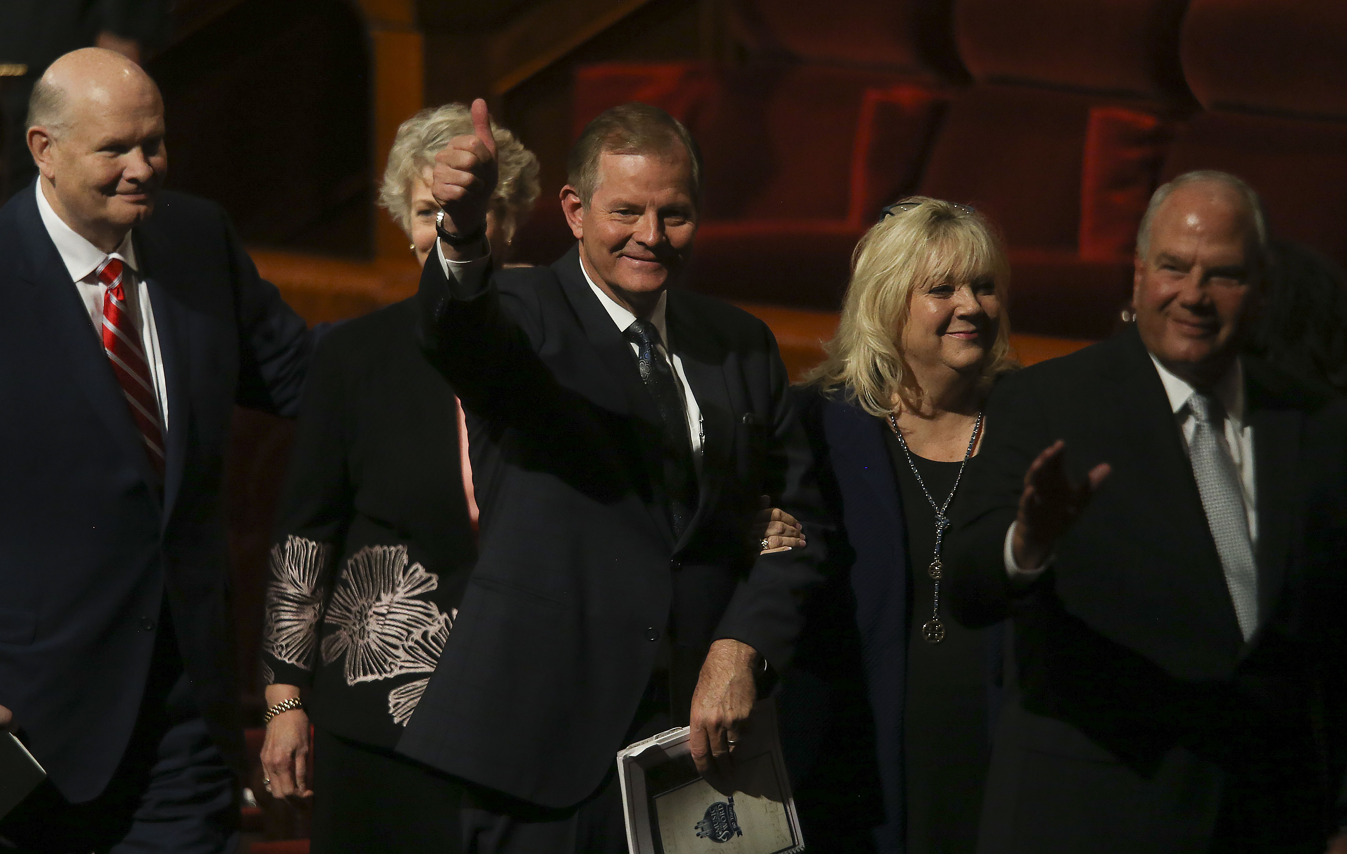 Elder Gary E. Stevenson of the Quorum of the Twelve Apostles, center, gives a thumbs-up with his wife, Lesa, as they leave the Sunday morning session of the 189th Semiannual General Conference of The Church of Jesus Christ of Latter-day Saints at the Conference Center in Salt Lake City on Sunday, Oct. 6, 2019.