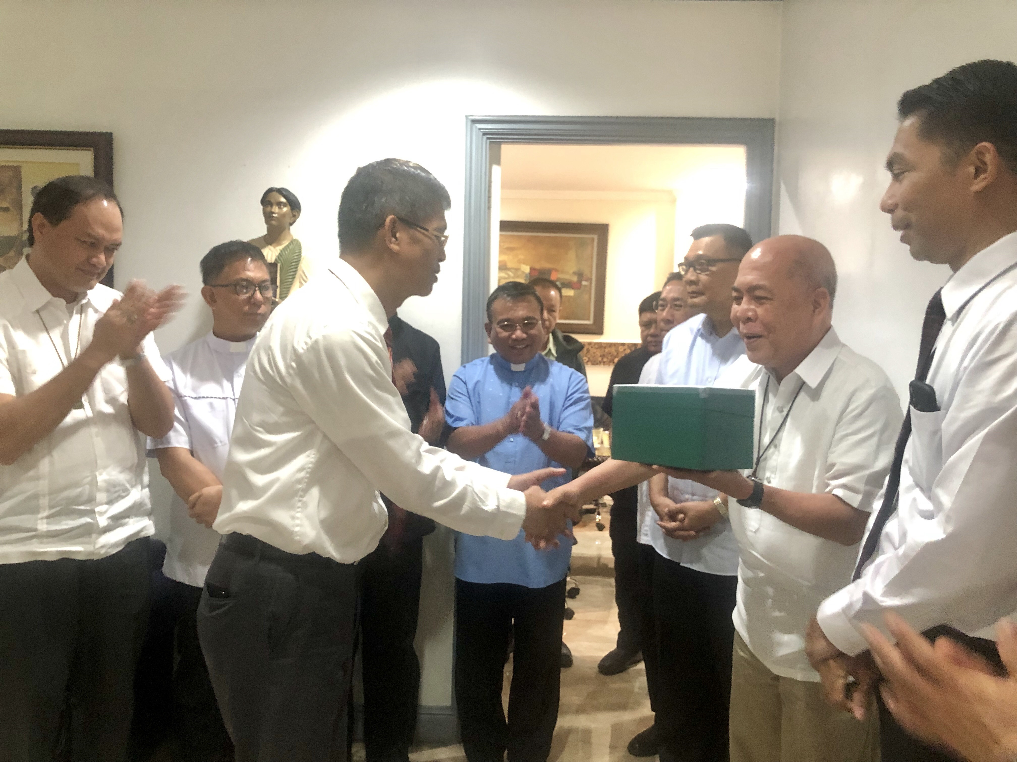 Elder Aretemio Maligon, Area Seventy, shakes the hand of Archbishop Romulo Valles, president of the Catholic Bishops' Conference of the Philippines (CBCP). Felvir Ordinario (extreme right), Family History manager, and other Catholic archbishops look on during the handover of the digitized records on Sept. 18 at CBCP headquarters.