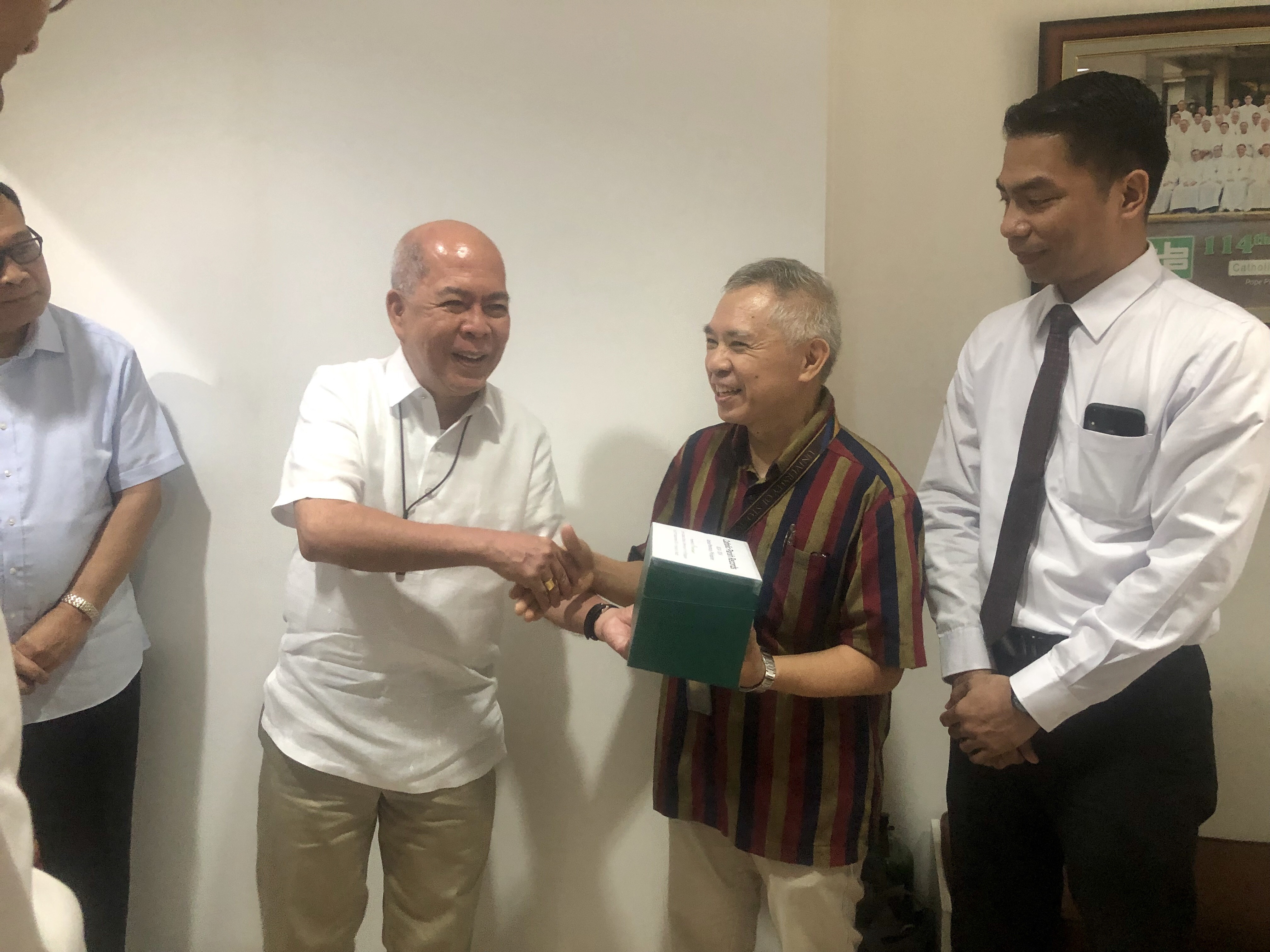 His Excellency, Archbishop Romulo Valles, turns over hard drives containing a collection of 14 million images to Archivist Professor Prof. Regalado Trota Jose of the Archives of the University of Santo Tomas (AUST), where the records will be stored.
