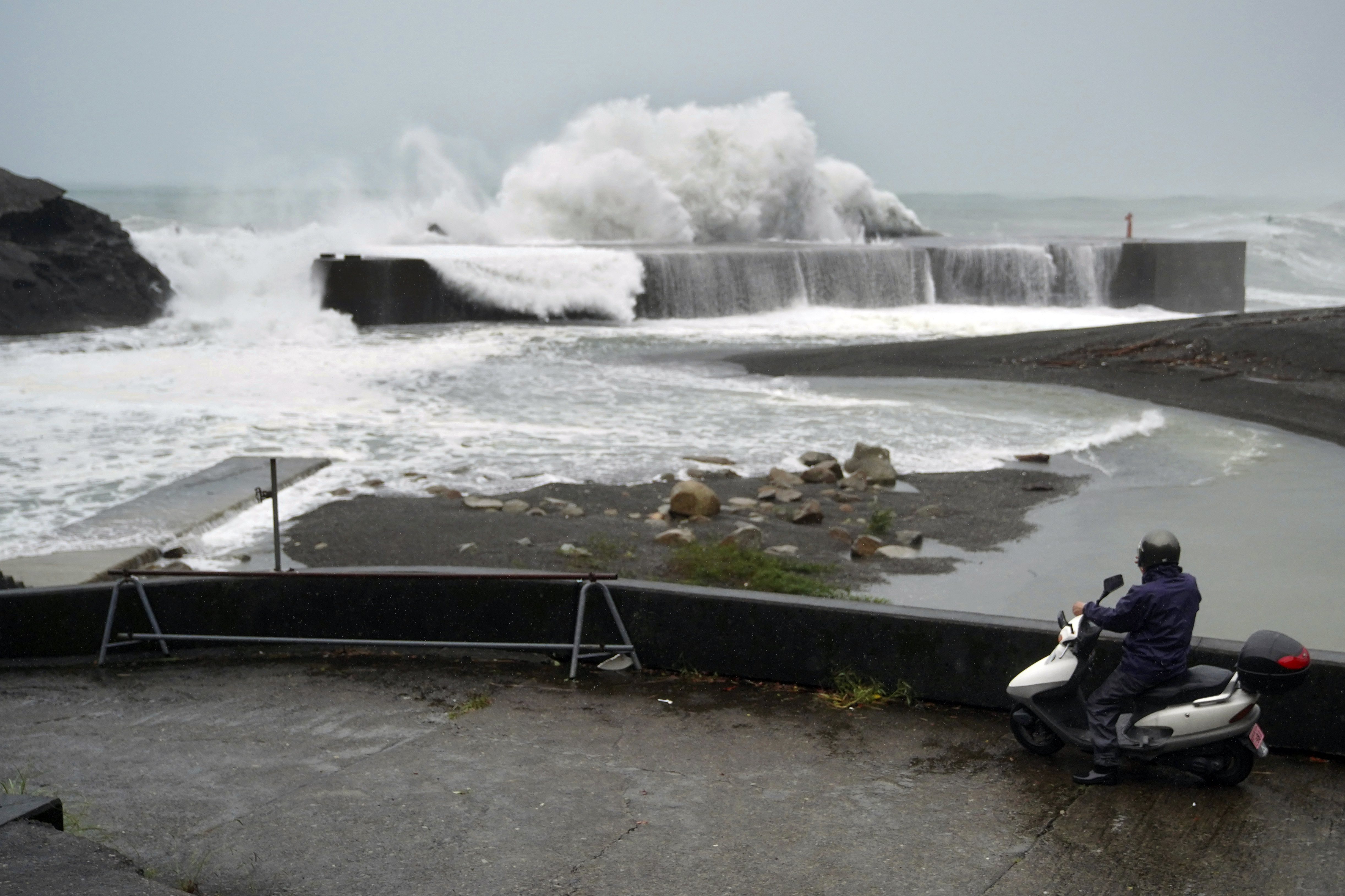 A man on a scooter watches as surging waves hit against the breakwater as Typhoon Hagibis approaches a port in Kumano, Mie Prefecture, Japan, Saturday, Oct. 12, 2019. (AP Photo/Toru Hanai)