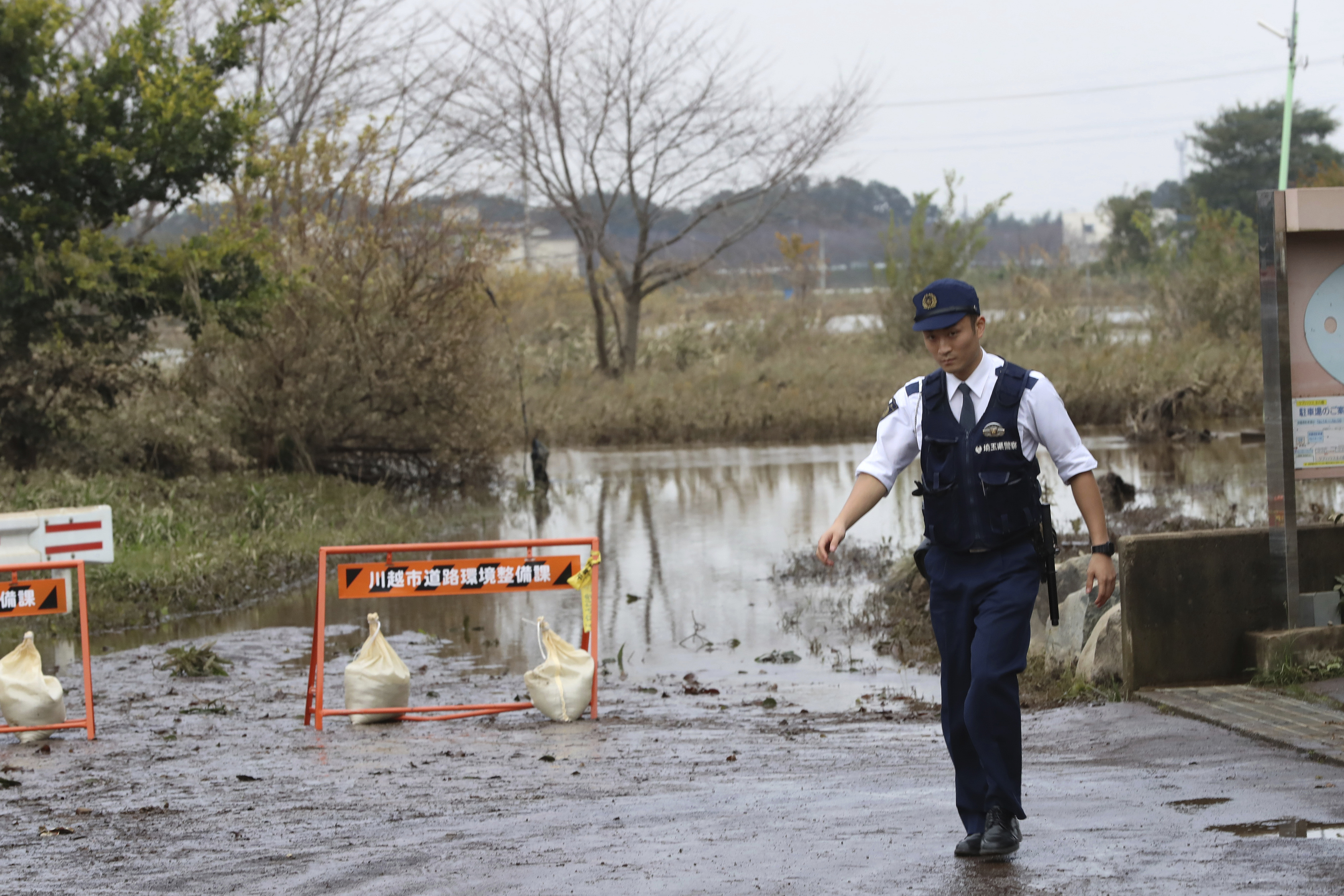 A police checks on a flooded street Monday, Oct. 14, 2019, in Kawagoe City, Japan. Typhoon Hagibis dropped record amounts of rain for a period in some spots, according to meteorological officials, causing more than 20 rivers to overflow. Some of the muddy waters in streets, fields and residential areas have subsided. But many places remained flooded, with homes and surrounding roads covered in mud and littered with broken wooden pieces and debris. (AP Photo/Eugene Hoshiko)