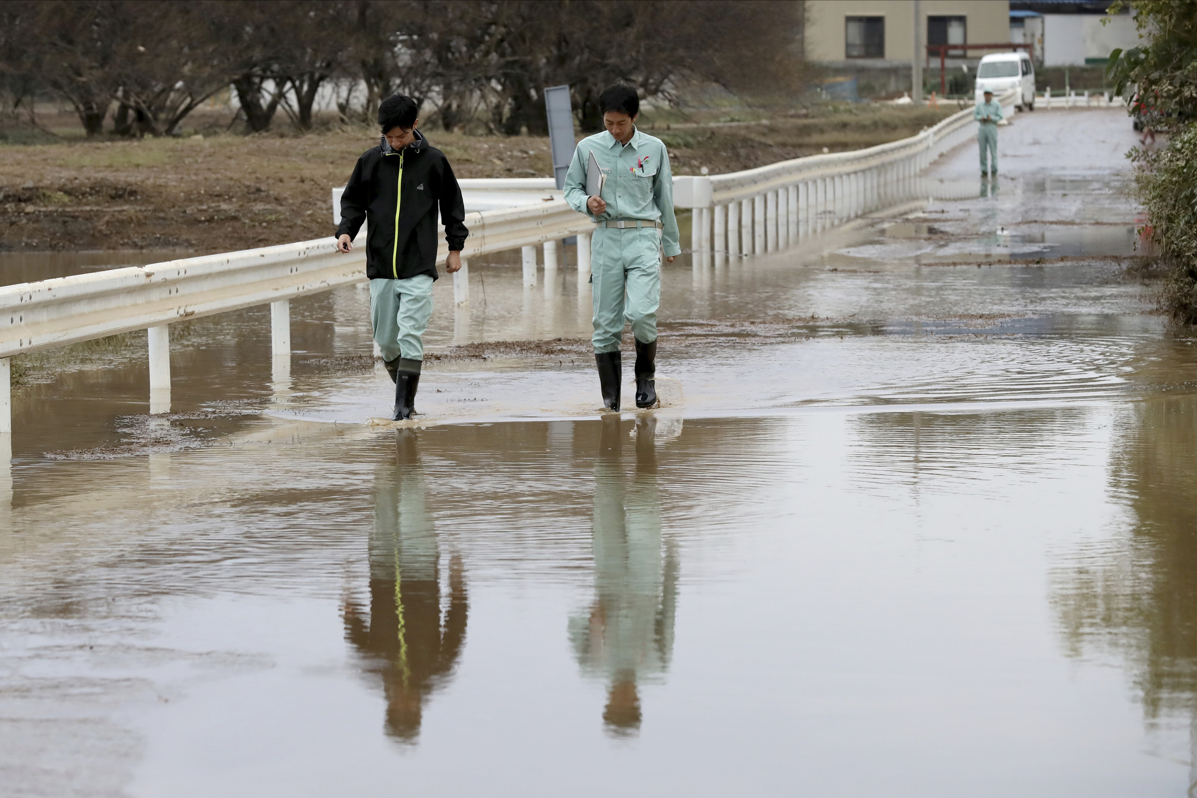 Workers survey a flooded street Monday, Oct. 14, 2019, in Kawagoe City, Japan. Rescue crews are digging through mudslides and searching near swollen rivers for missing people after Typhoon Hagibis caused serious damage in central and northern Japan. Dozens of people are dead or missing. (AP Photo/Eugene Hoshiko)