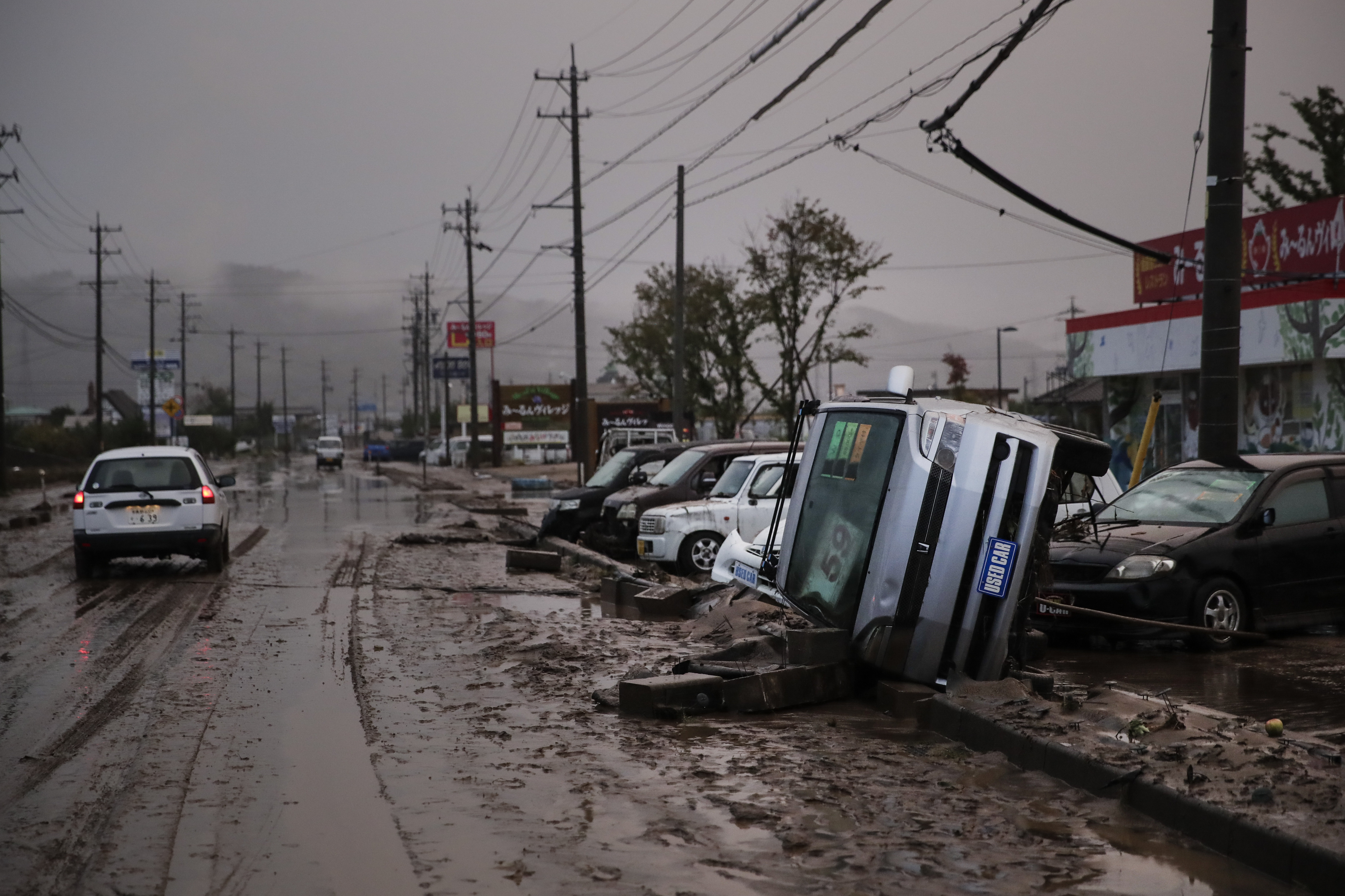 Typhoon-damaged cars sit on the street covered with mud Monday, Oct. 14, 2019, in Hoyasu, Japan. Rescue crews in Japan dug through mudslides and searched near swollen rivers Monday as they looked for those missing from typhoon Hagibis that left as many as 36 dead and caused serious damage in central and northern Japan. (AP Photo/Jae C. Hong)