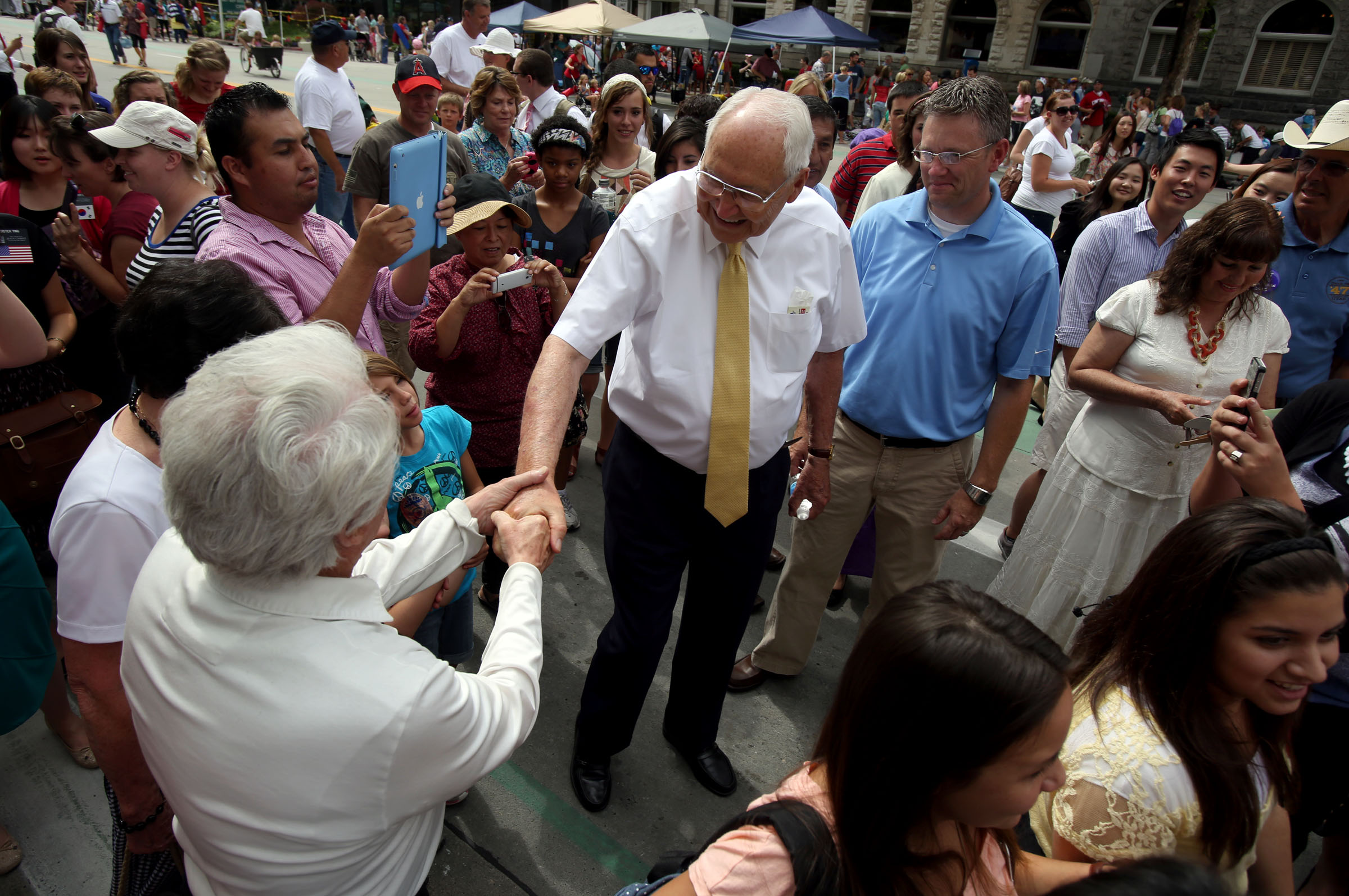 Elder L. Tom Perry is surrounded by people who want to talk to him as he leaves the Days of '47 Parade in Salt Lake City on Wednesday, July 24, 2013.
