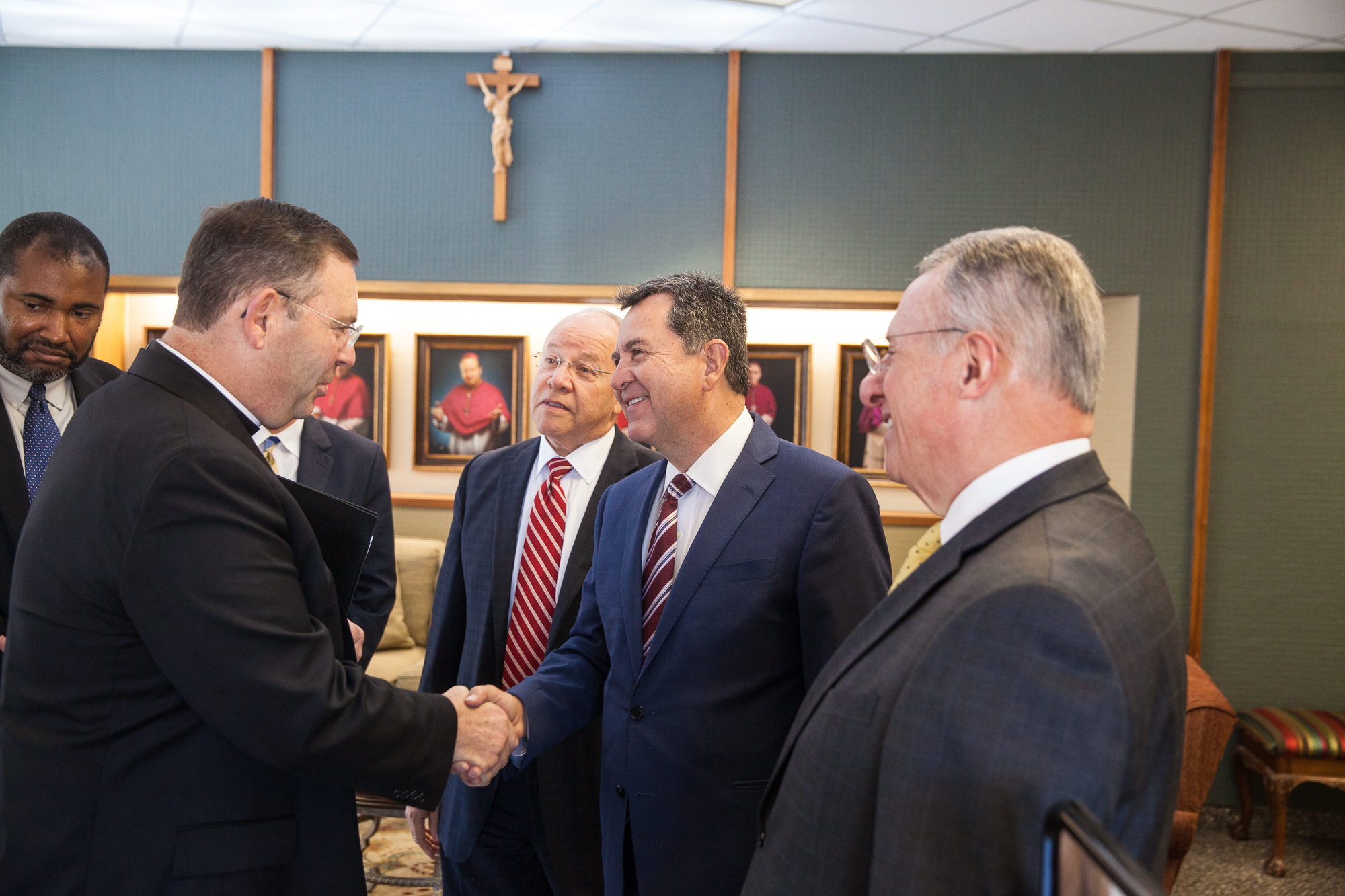 Elder Adrian Ochoa shakes hands with Father James Misko, Vicar General of the Catholic Diocese of Austin, during a visit to the Pastoral Center with Elder Ulisses Soares on October 18, 2019.