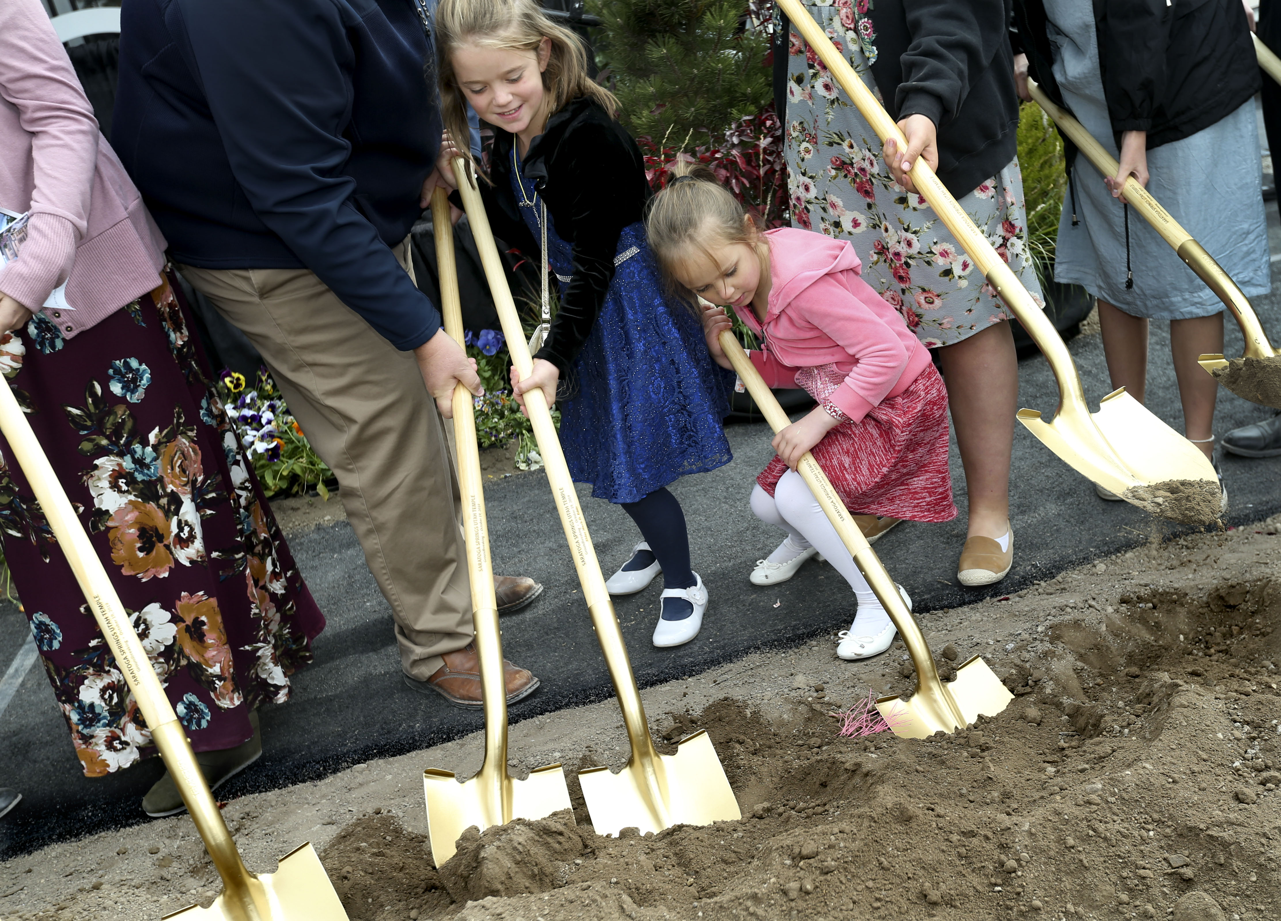 Sisters Aubrey and Lauren Kenney of Eagle Mountain throw dirt during the groundbreaking ceremony for the Saratoga Springs Utah Temple on Saturday, Oct. 19, 2019.