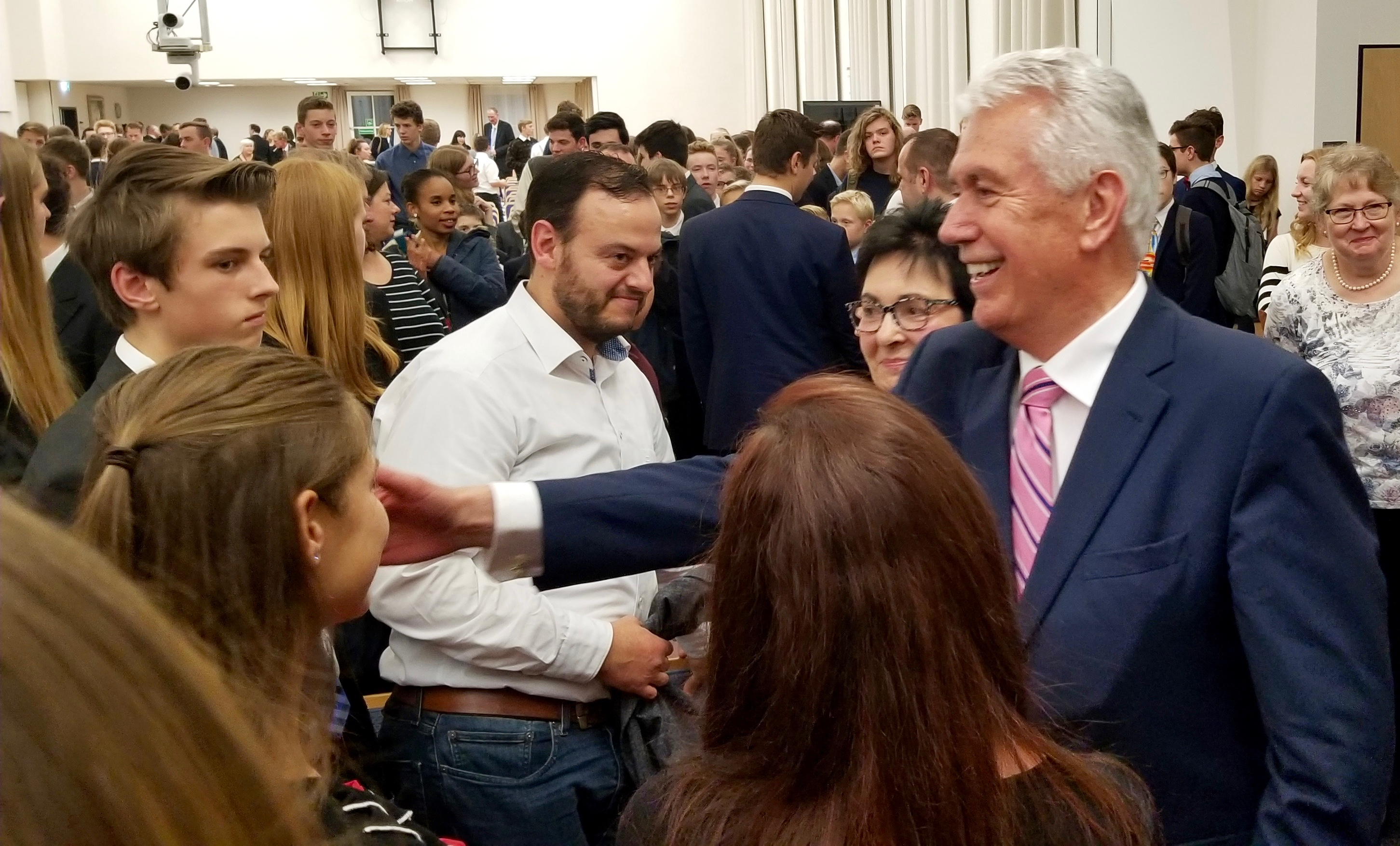 Elder Dieter F. Uchtdorf of the Quorum of the Twelve Apostles reaches out as he and his wife, Sister Harriet Uchtdorf greet attendees after a youth devotional in Friedrichsdorf, Germany, on Saturday, Oct. 19, 2019, the eve of the Frankfurt Germany Temple rededication.