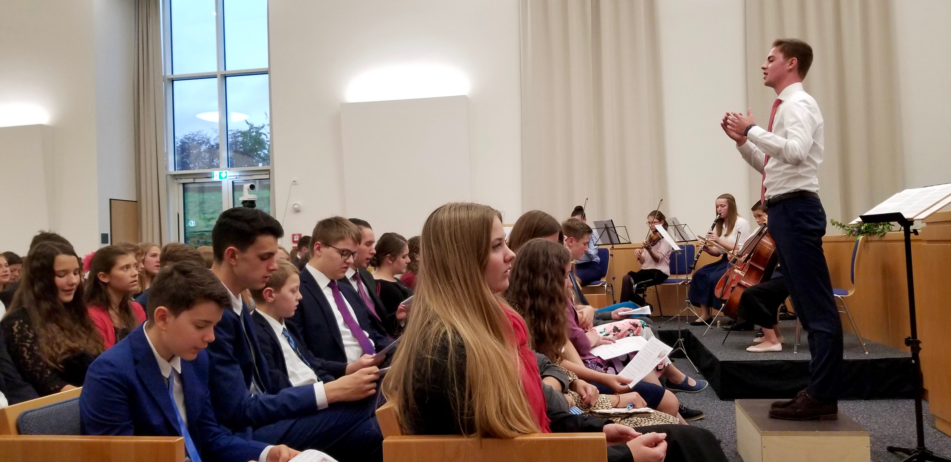 "Attendees join a small orchestral group and the choir in singing ""Families Can Be Together Forever"" at the youth devotional in Friedrichsdorf, Germany, on Oct. 19, 2019, the eve before the rededication of the Frankfurt temple."